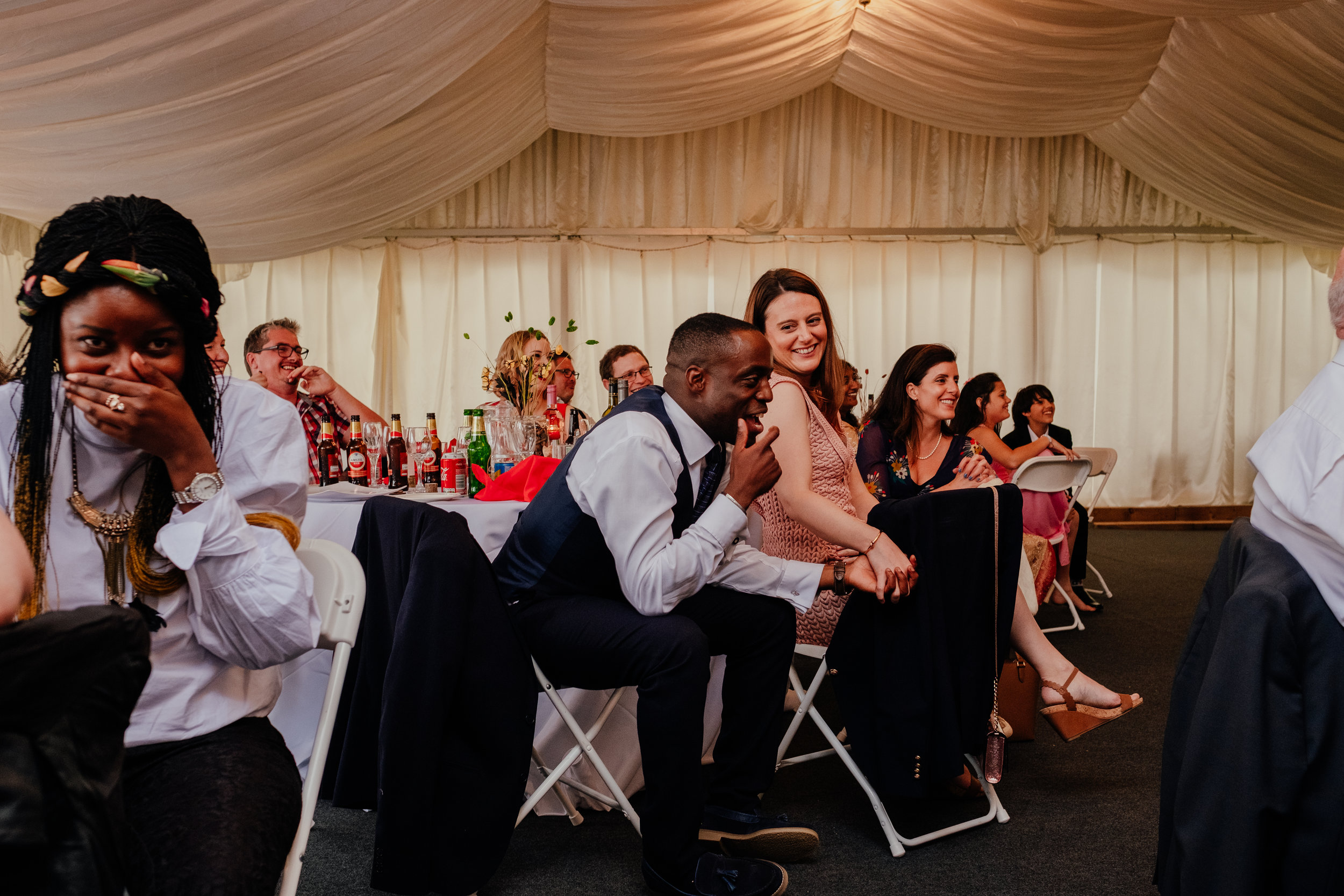 Wedding guests laughing during wedding reception