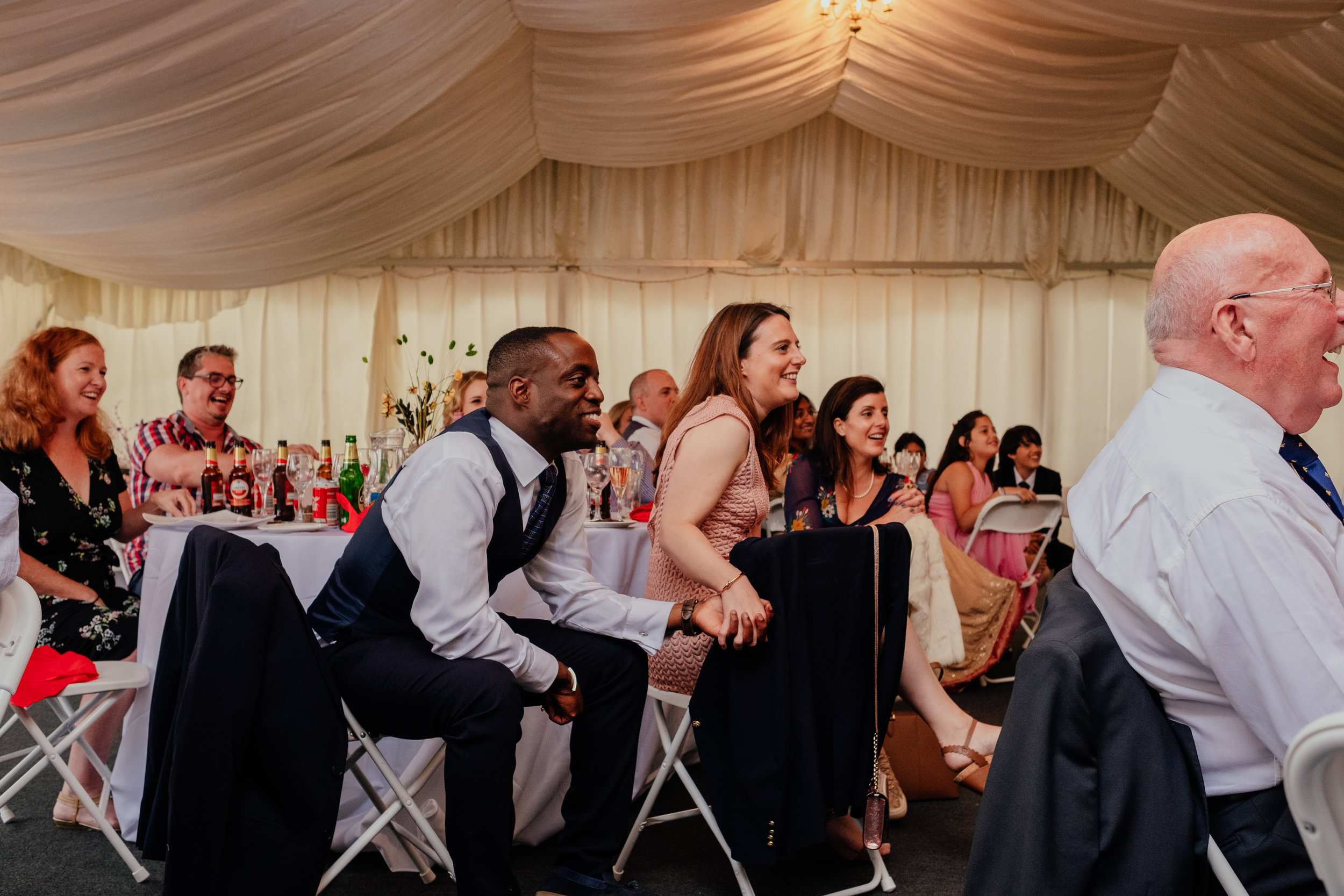 Guests holding hands and laughing during wedding reception