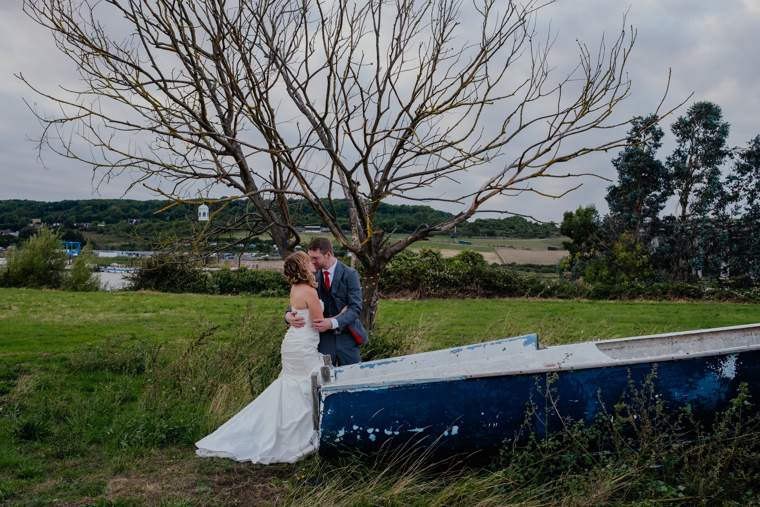 Bride and groom stood next to boat
