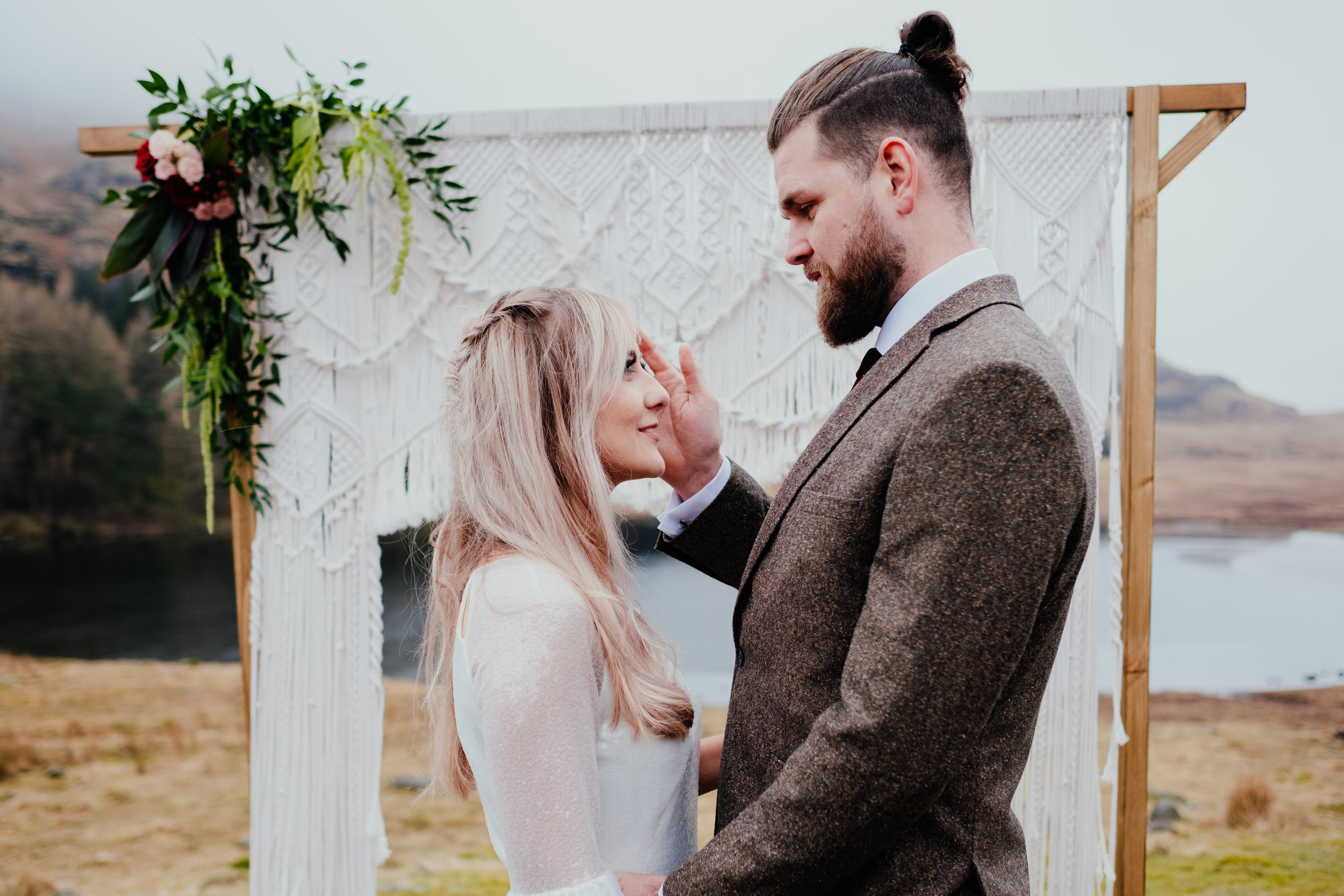 Groom pushes bride's hair out of her face during Lake District elopement