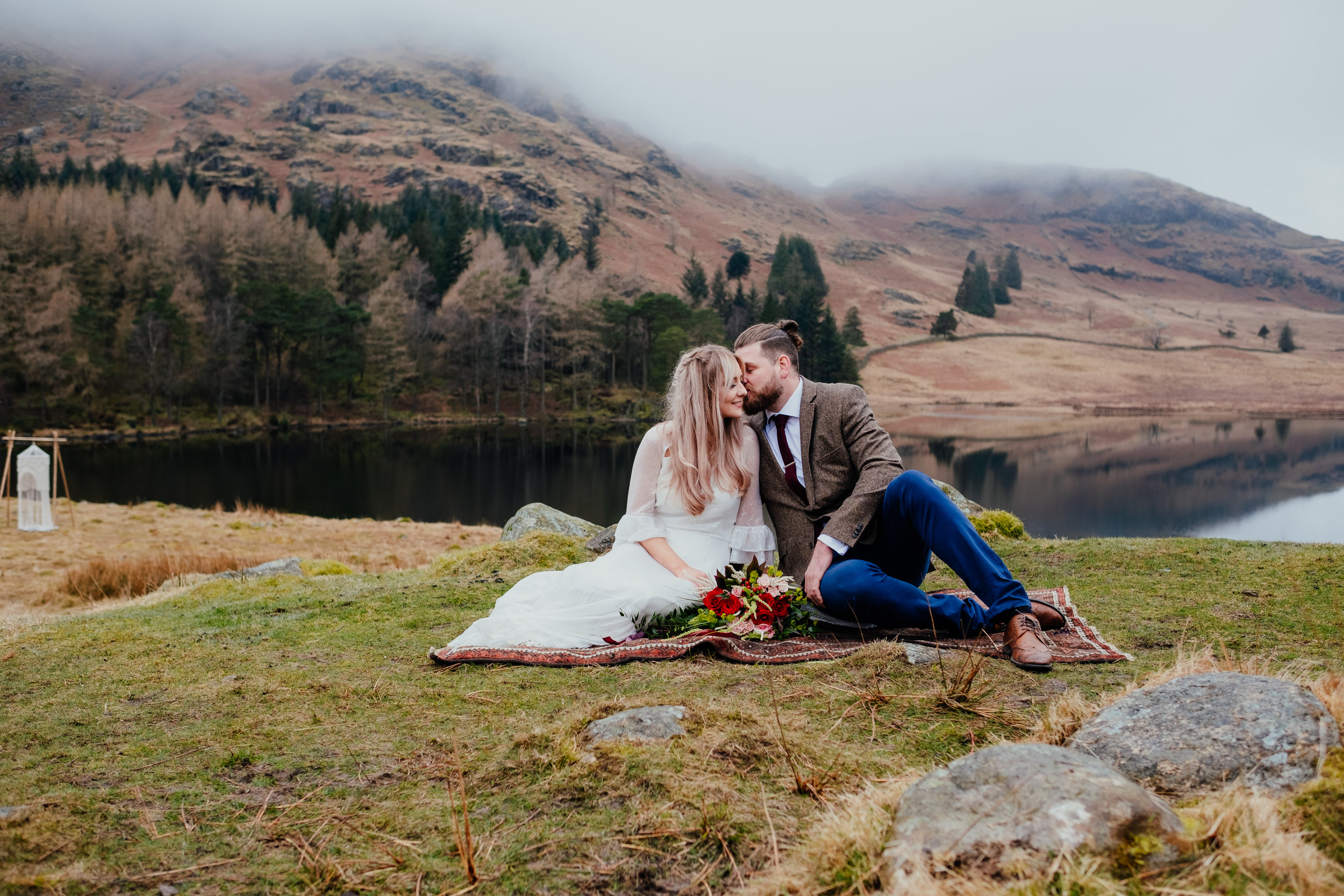 Bride and groom sat on blanket during Lake District elopement at Blea Tarn