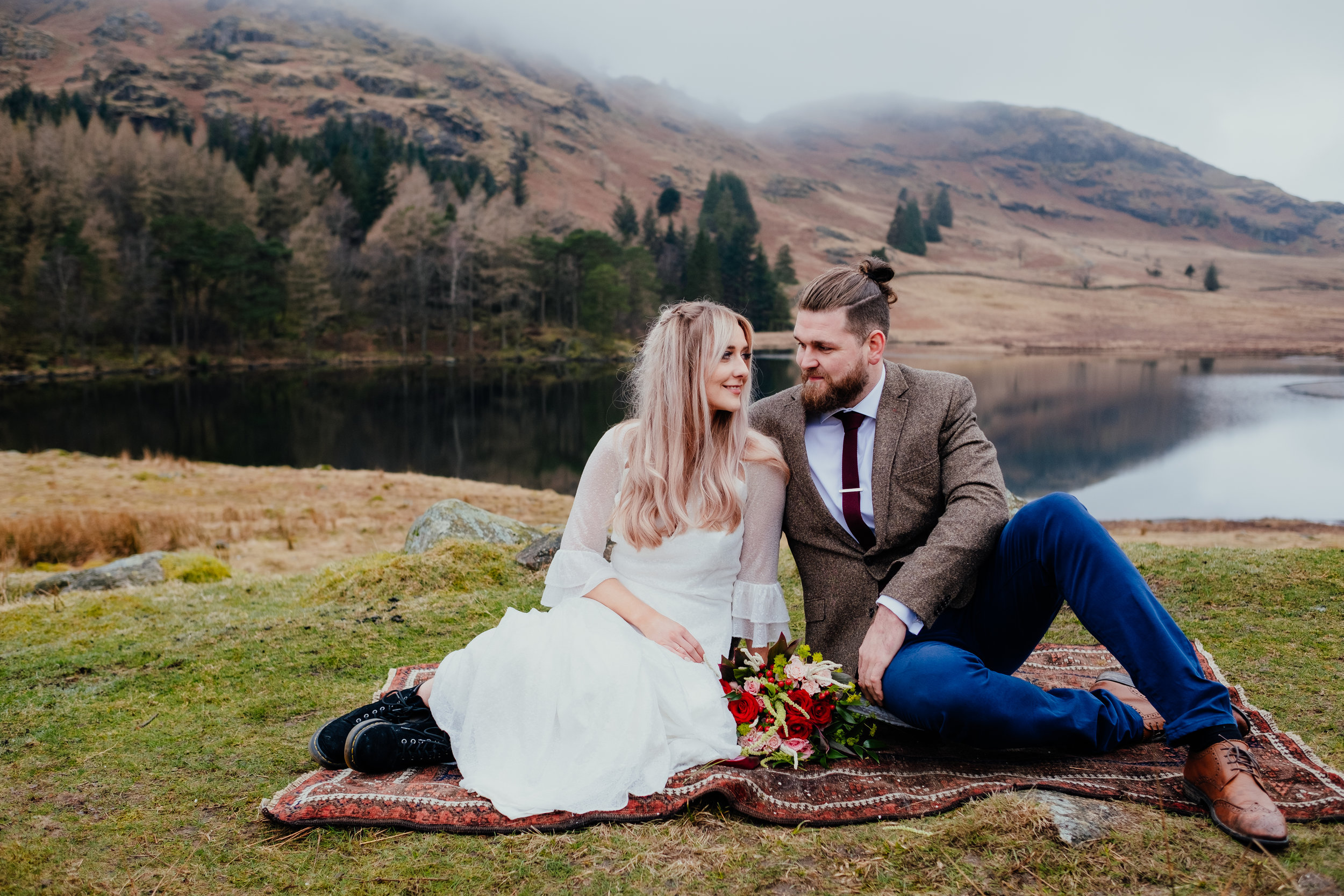 Bride and groom looking at each other and smiling sat on a rug at Lake District elopement UK
