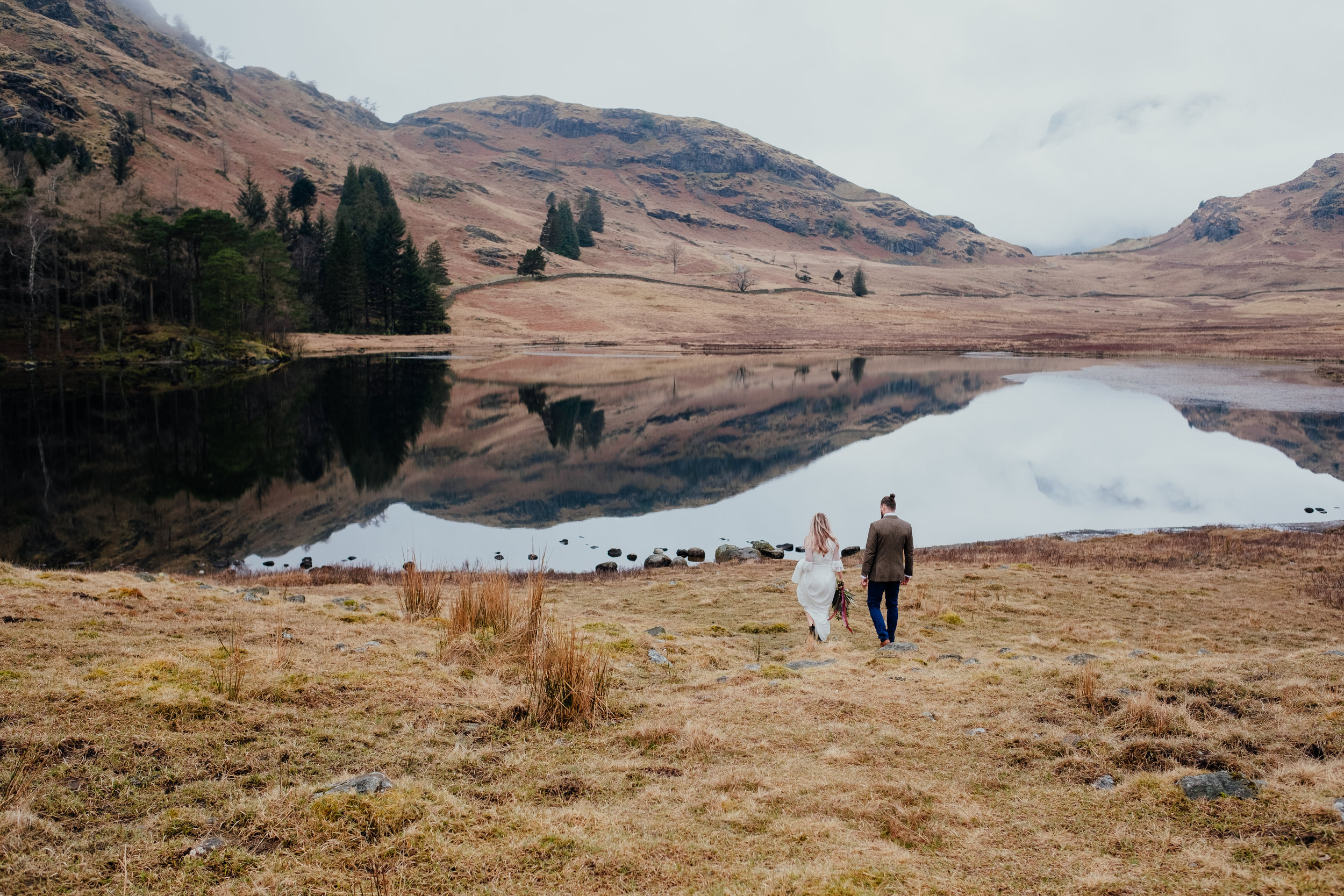 Bride and groom walking through Blea Tarn in the Lake District