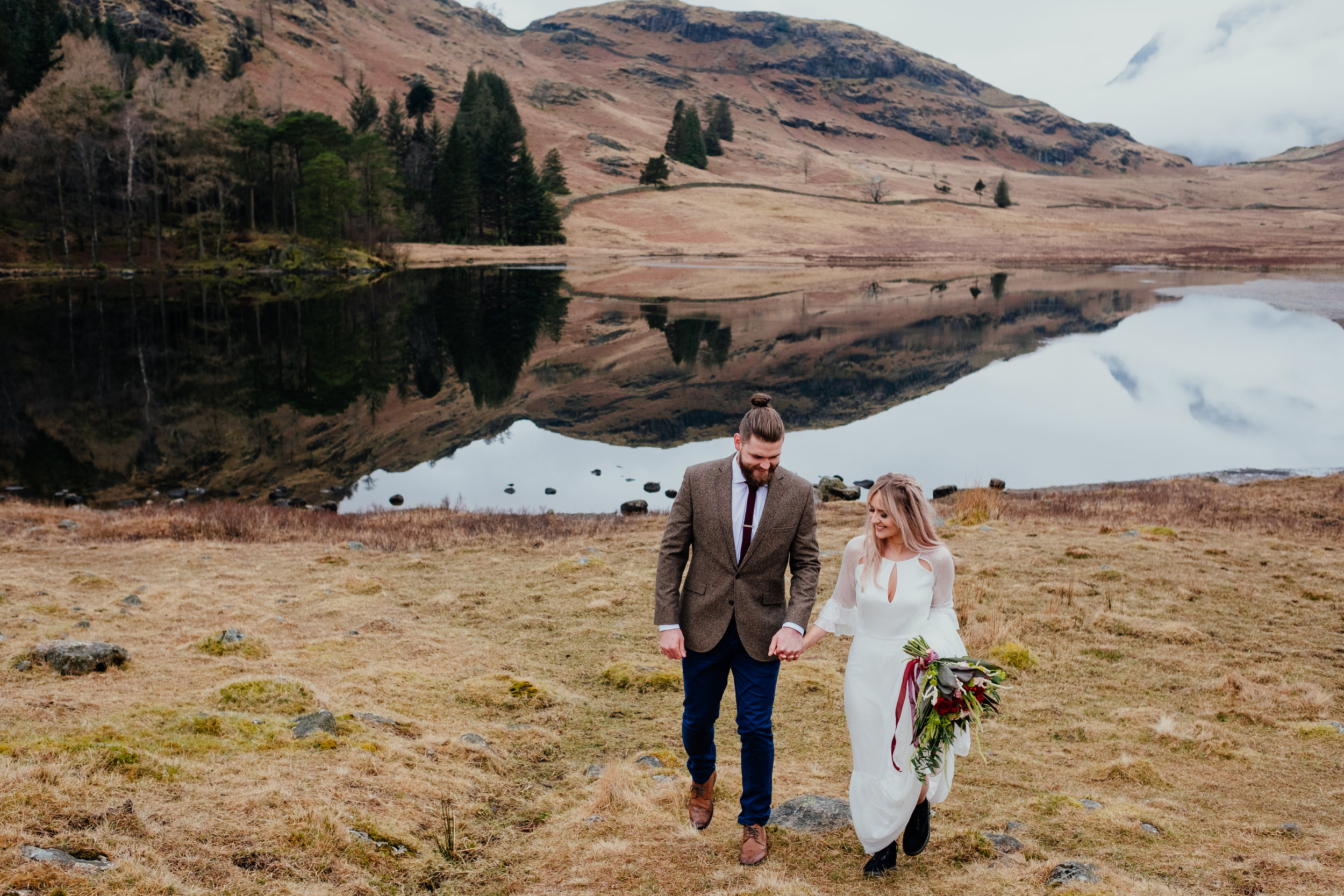 Bride and groom walking holding hands during Lake District elopement