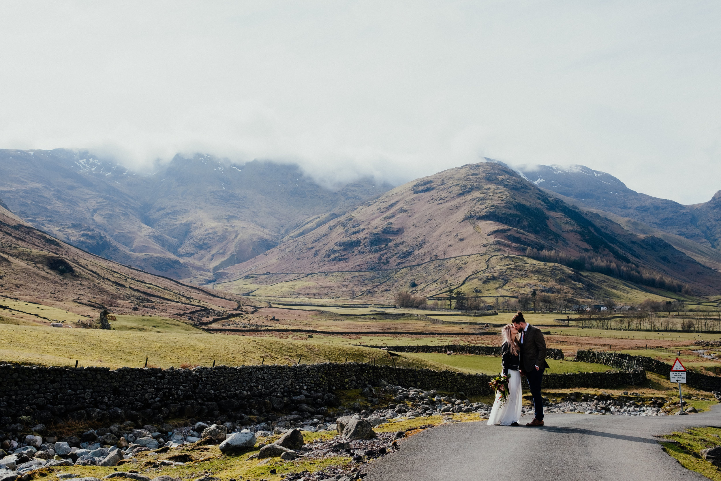 Bride and groom kissing in the Lake District with mountains behind them