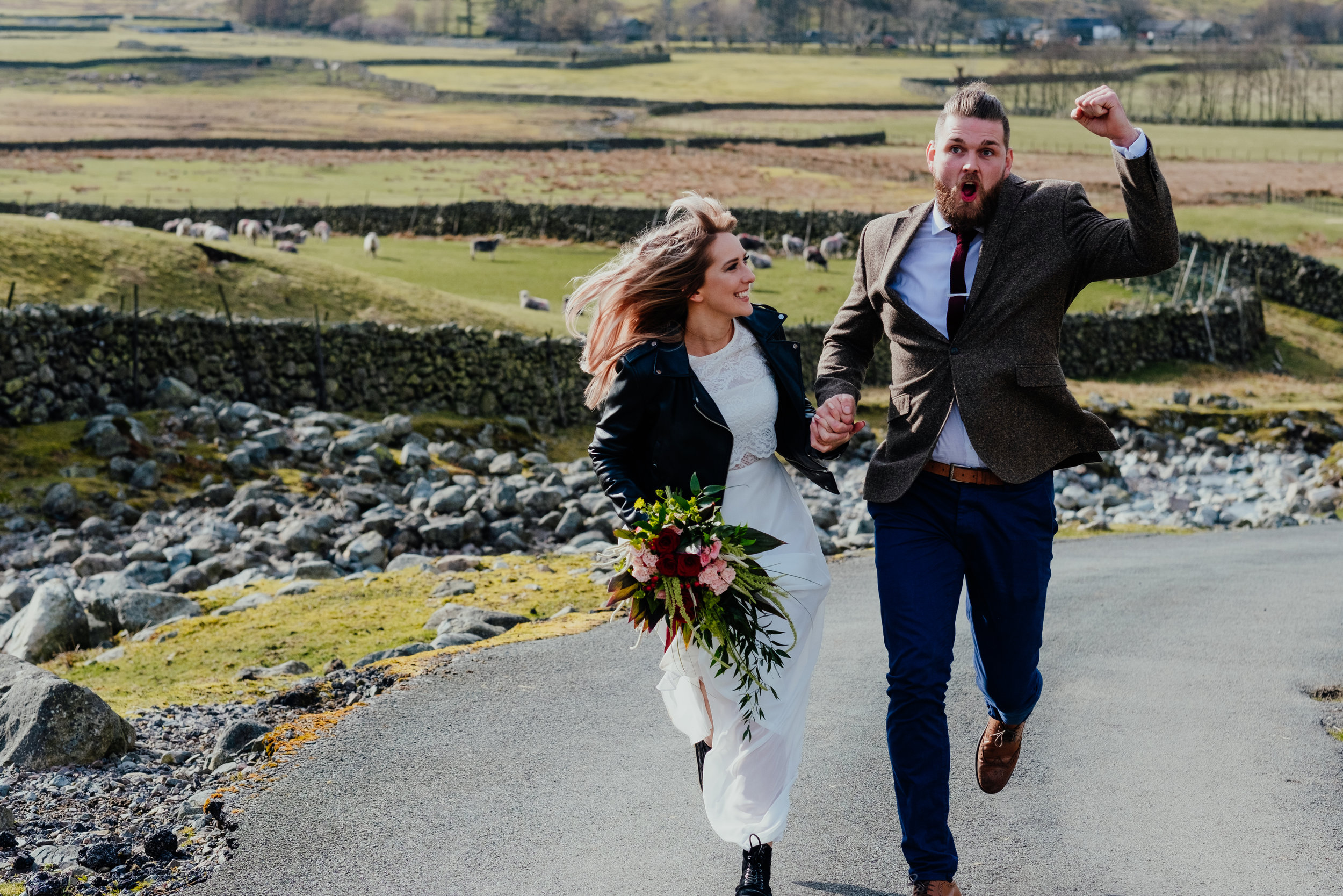 Groom fist pumping while he and bride run along hand in hand