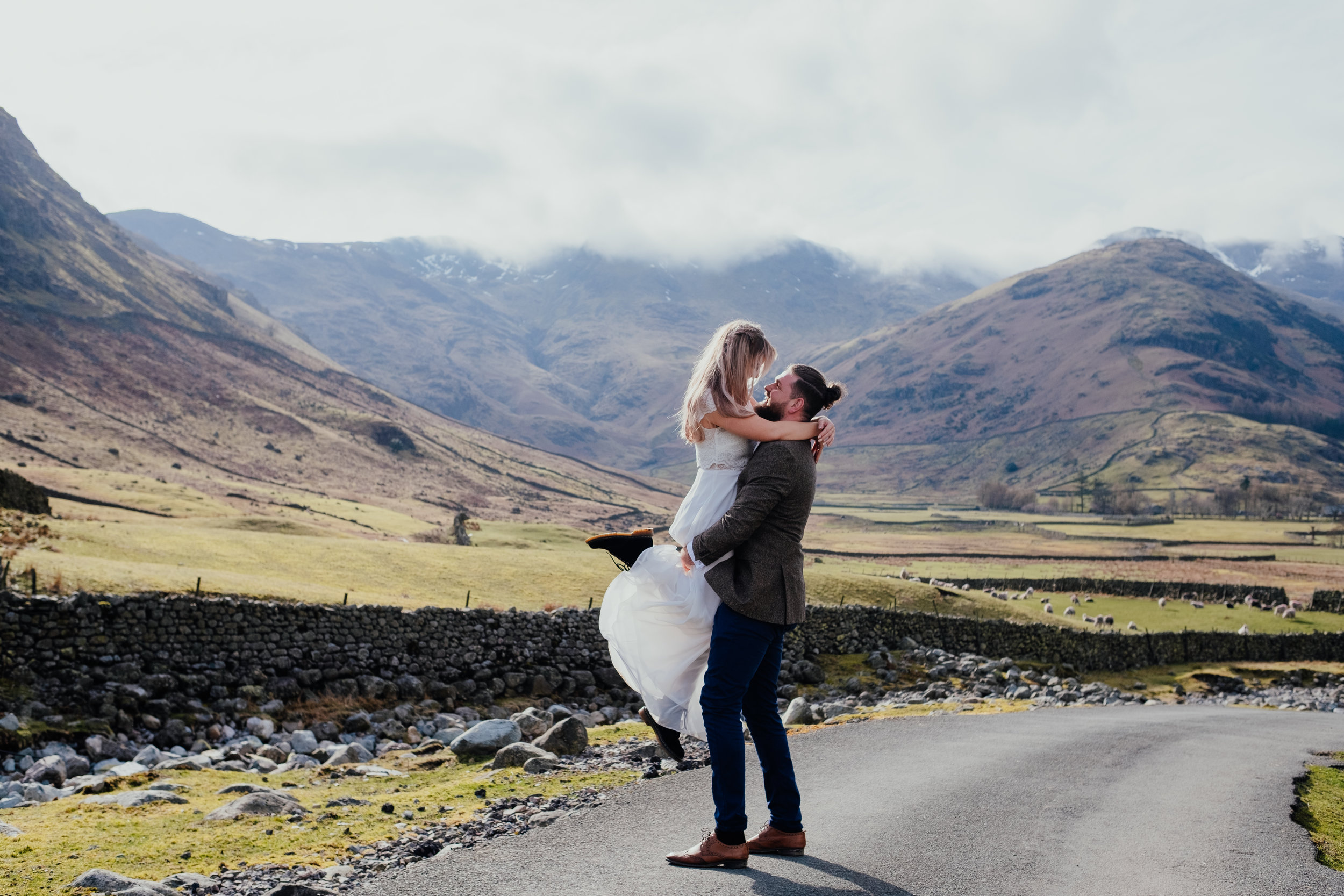 Groom lifts bride up in his arms in the Lake District