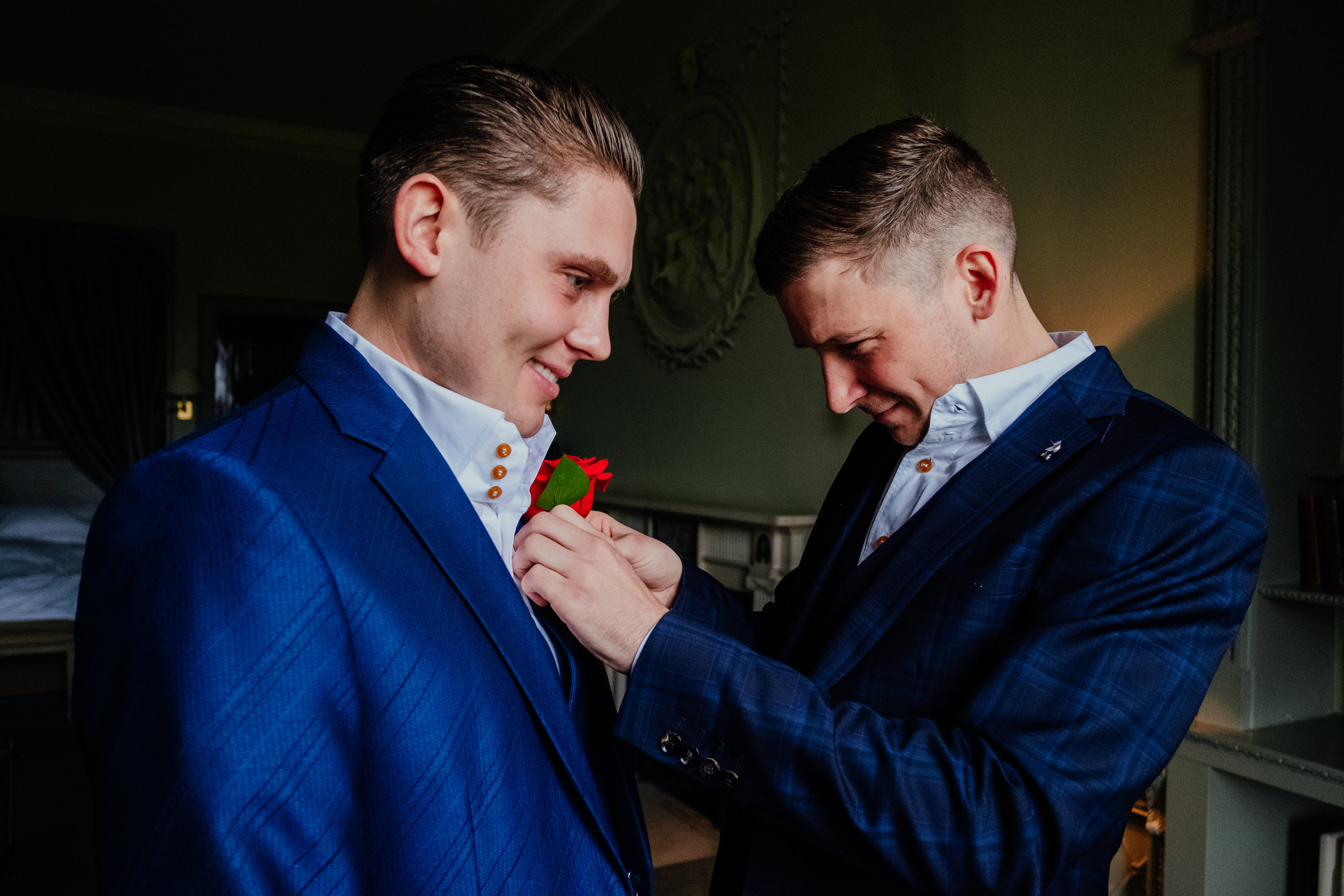Buxted House Day of the Dead autumn wedding Groomsmen helps Groom put on rose buttonhole