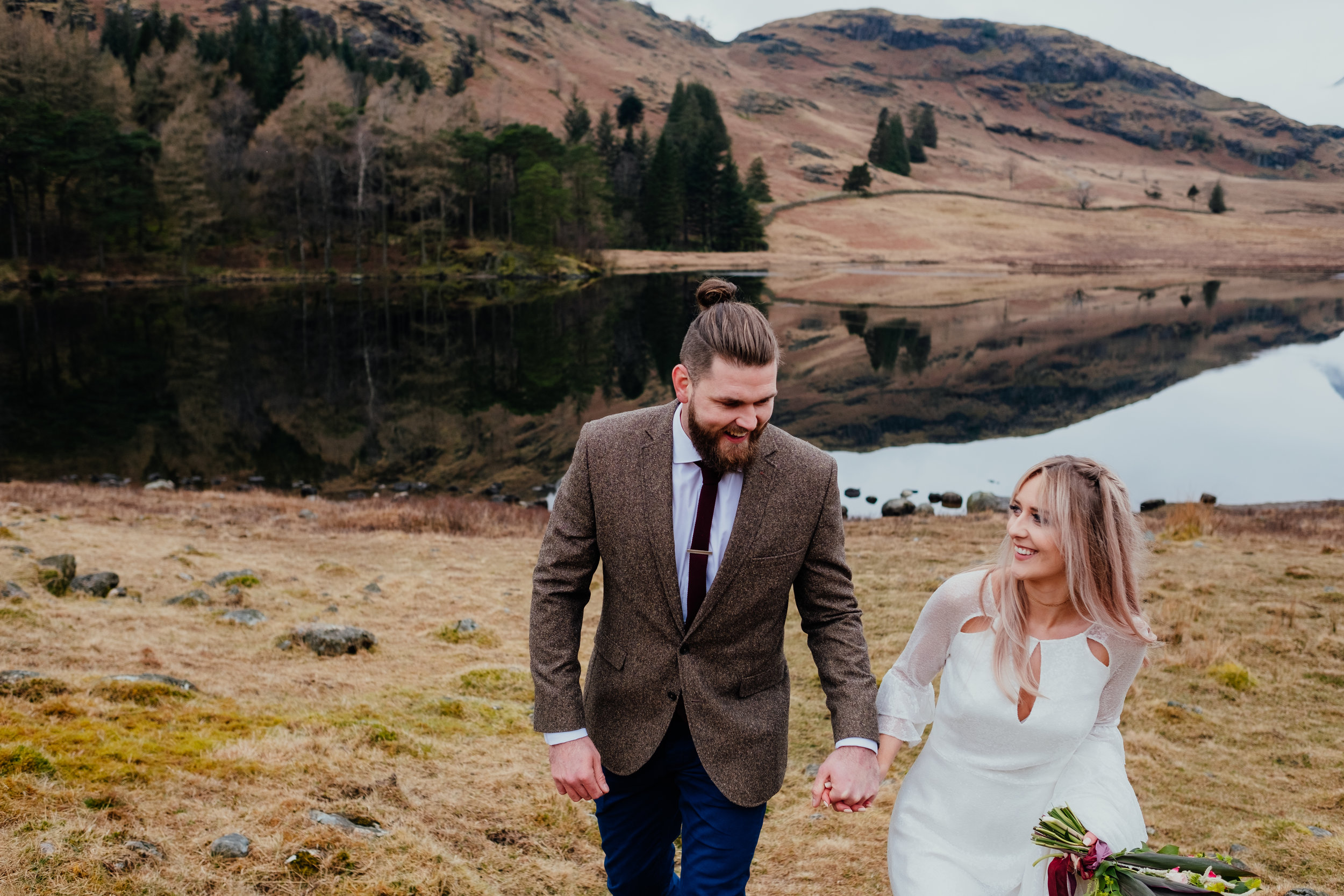 Lake District elopement boho bride and groom walking away from lake