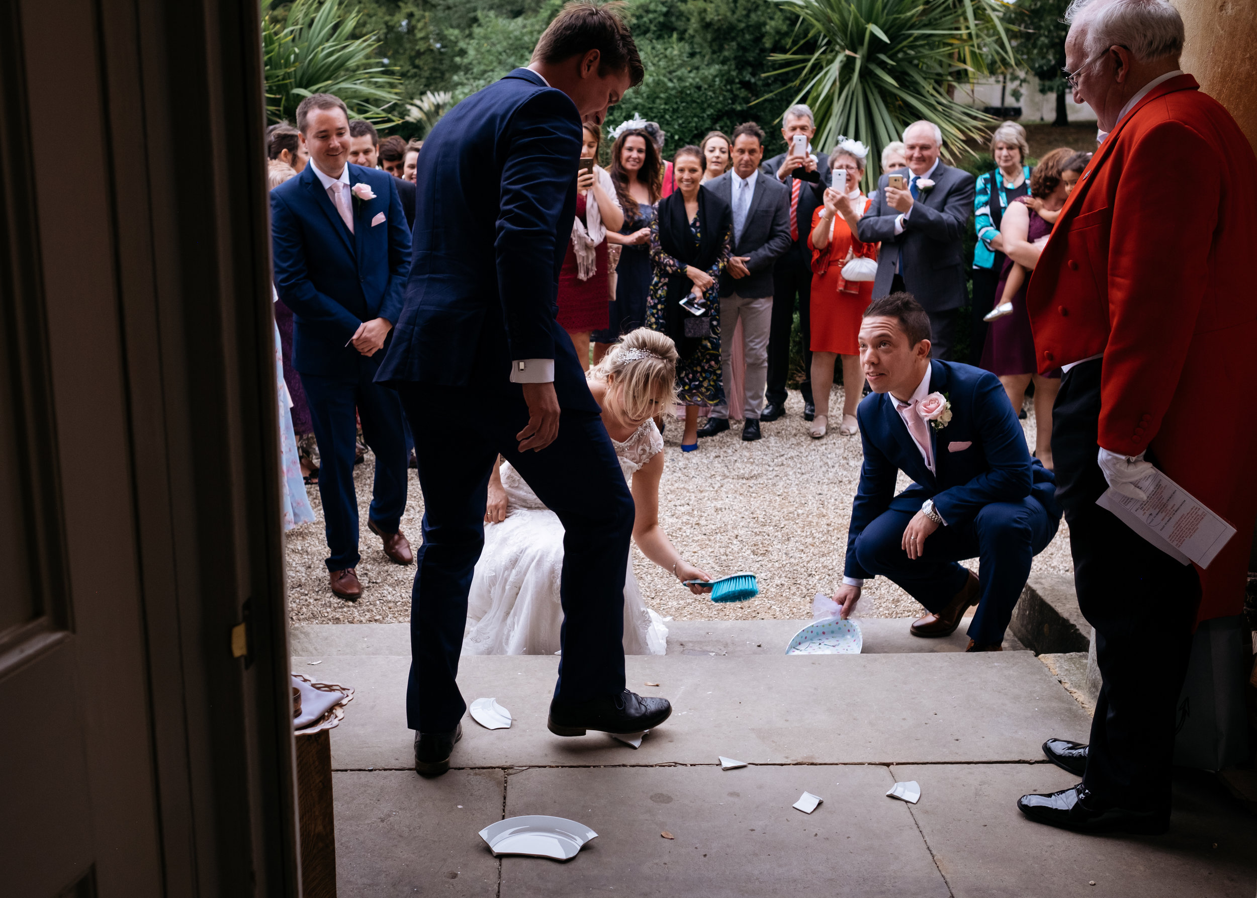Bride and groom drop plates, an Eastern European wedding tradition and the best man treads on the broken pieces