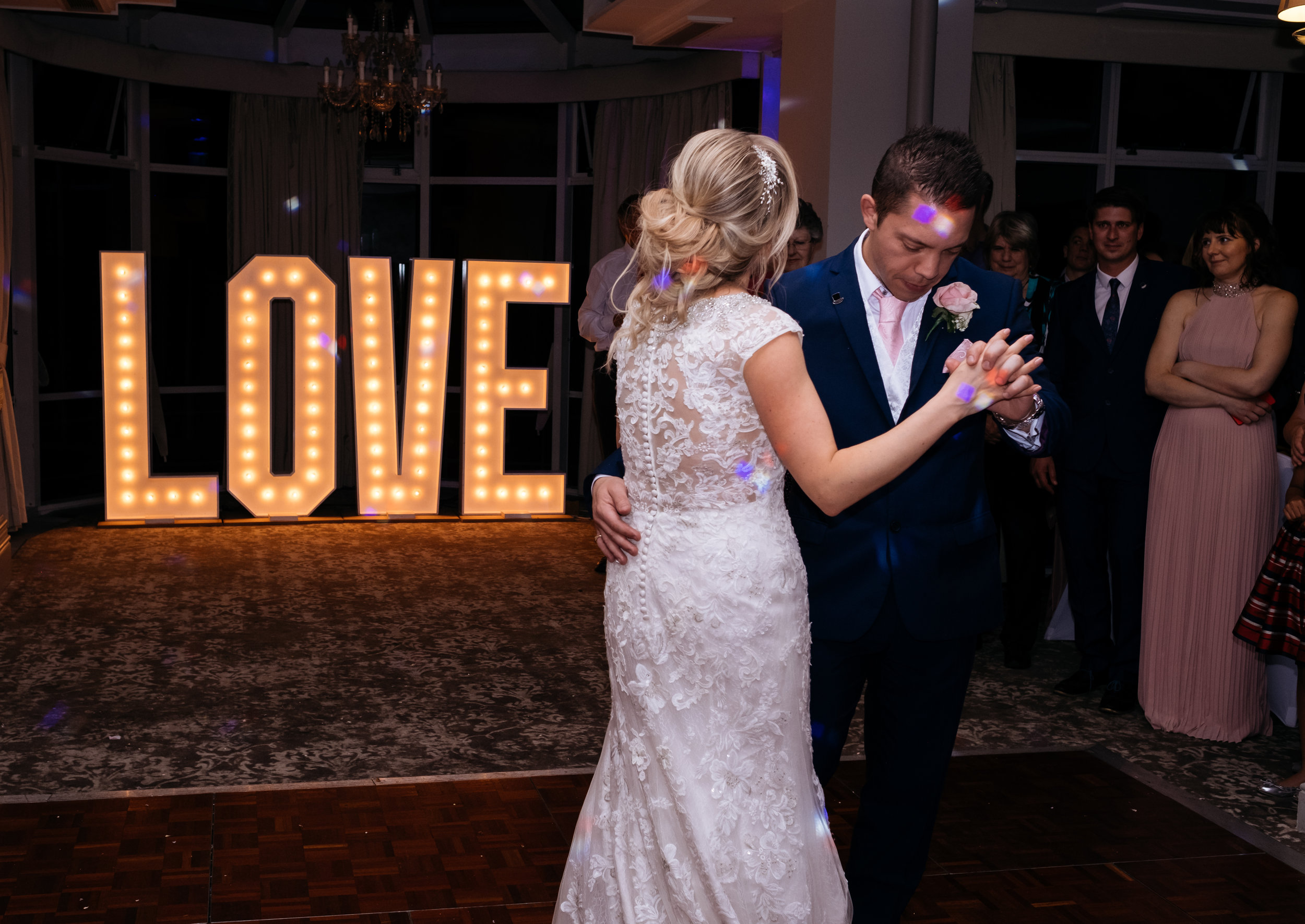 Bride and groom first dance at Mercure Newbury Elcot Park Hotel wedding with giant LOVE lit up sign