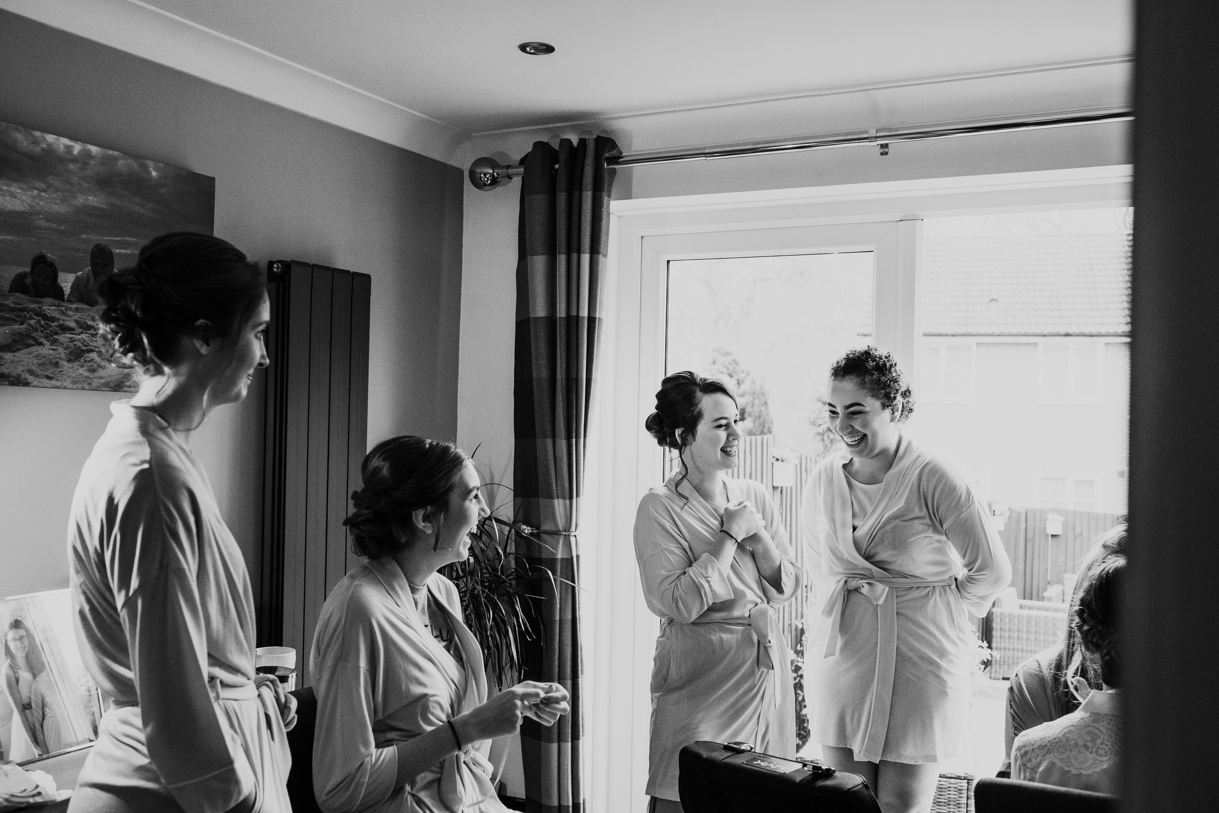 Bridesmaids laughing while bride has make up done