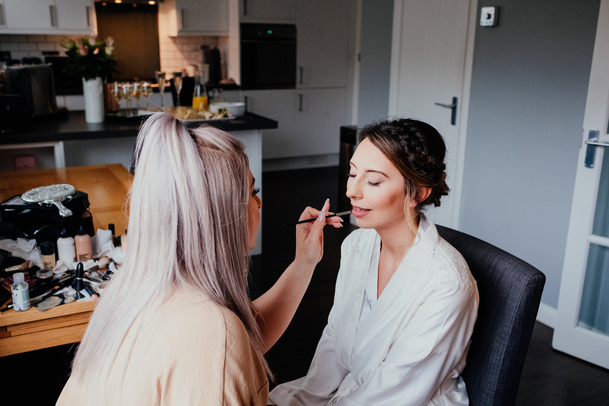 Bride having her make up applied by make up artist on the morning of her wedding