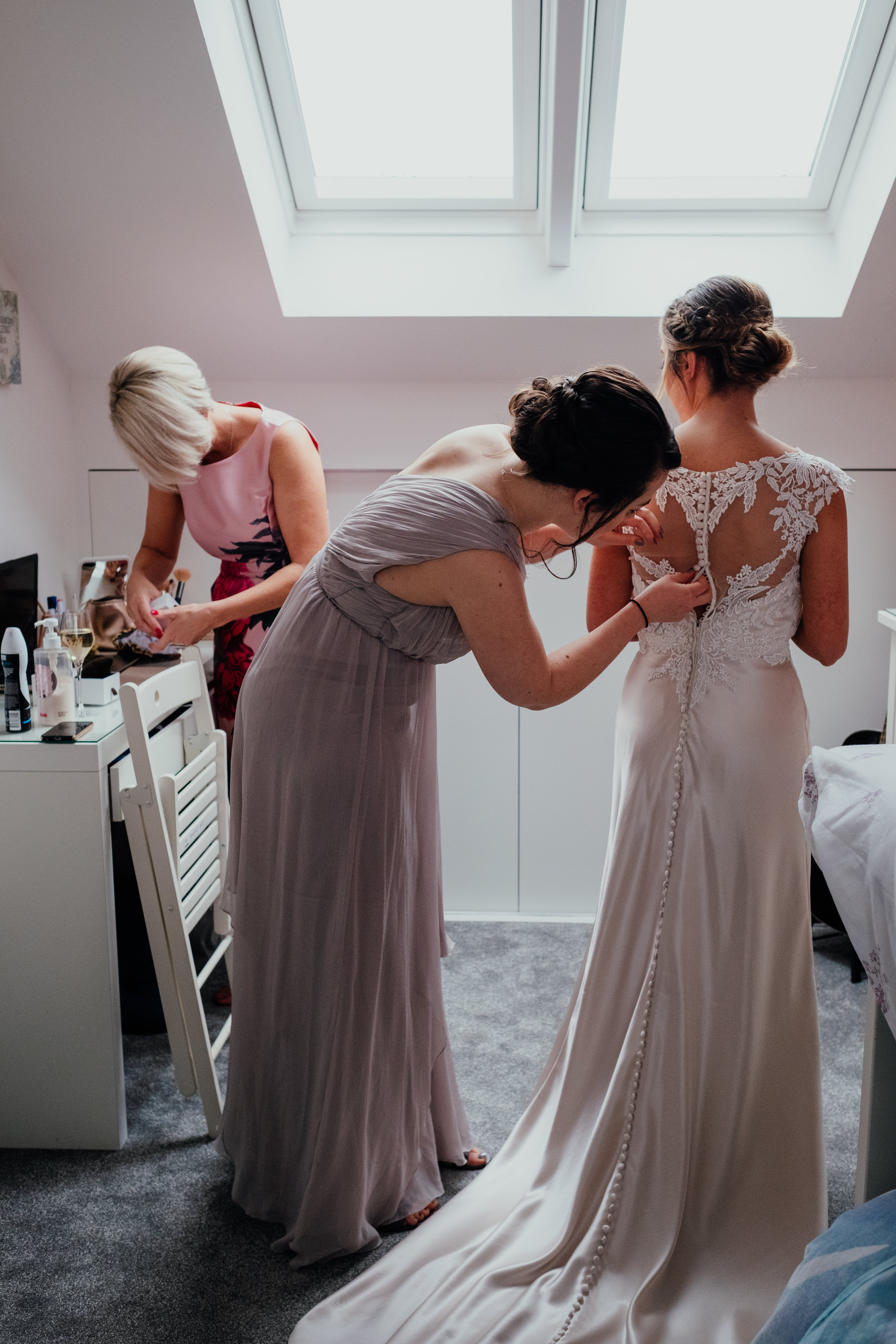 Mother of the Bride and Bridesmaid help Bride put on wedding dress