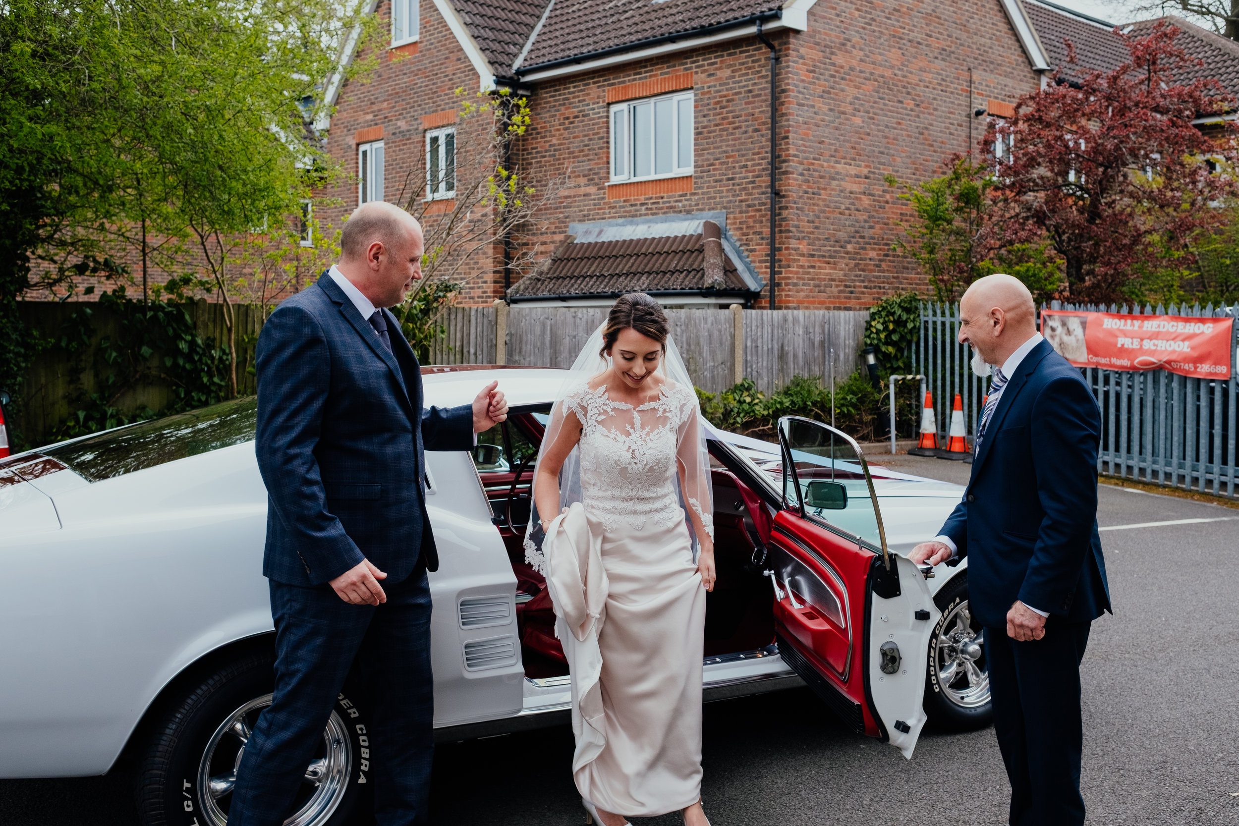 Bride and Father of the Bride arrive at the church in a mustang wedding car