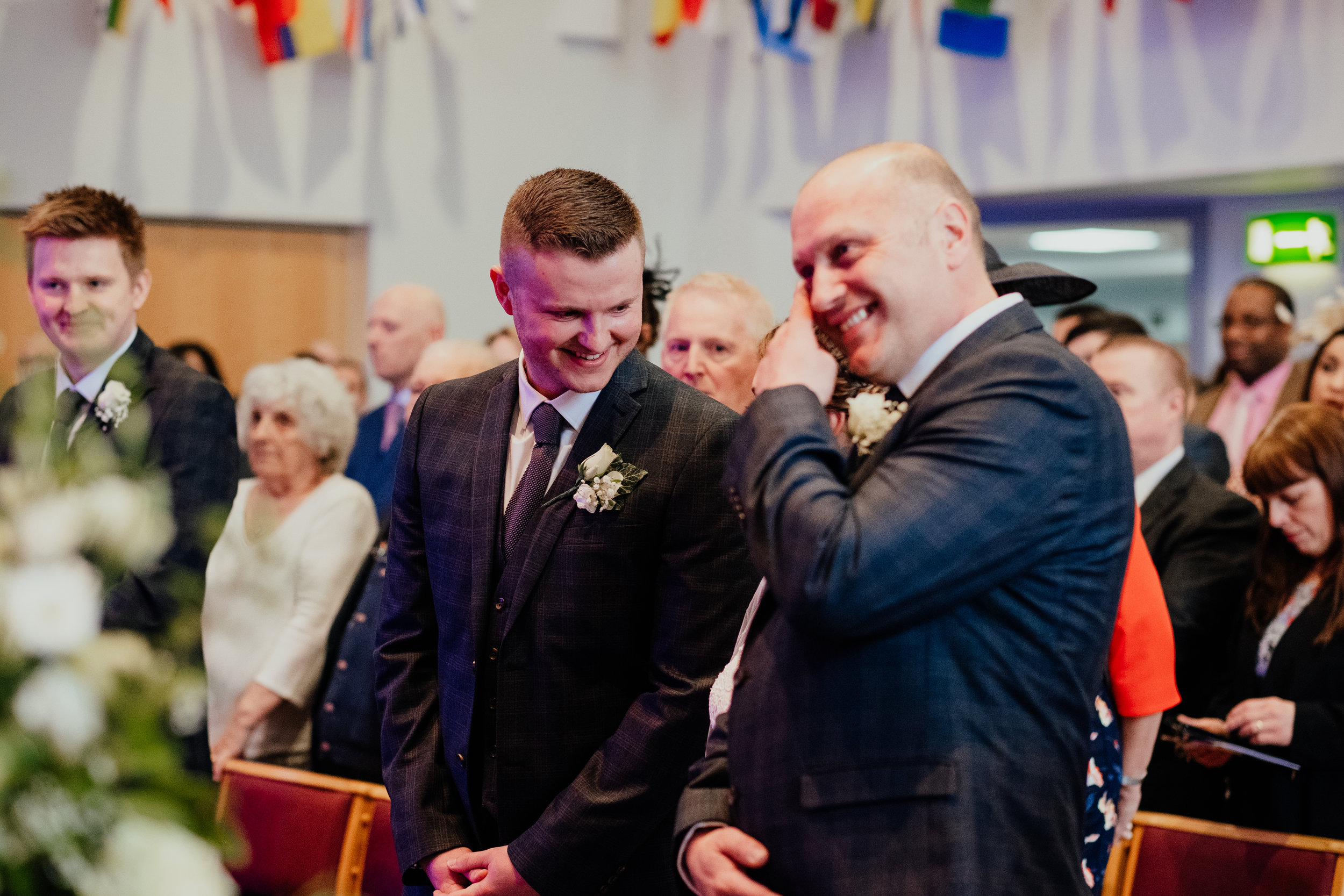Groom smiles at Bride as Father of Bride wipes a tear from his eyes and smiles