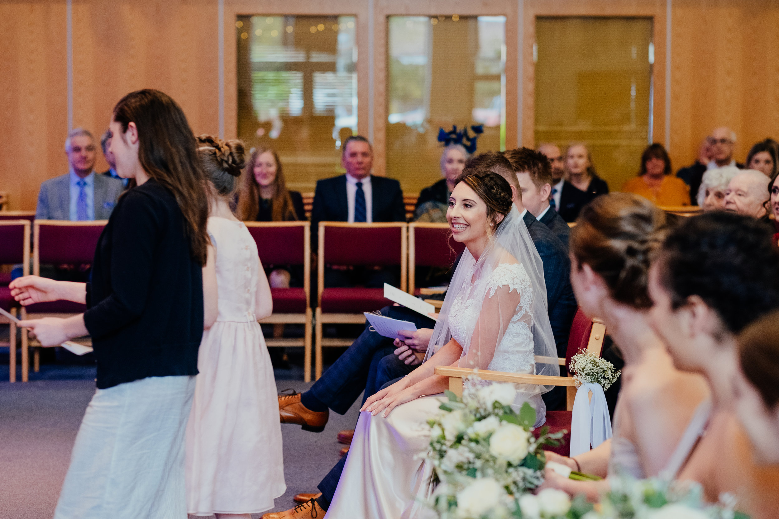 Bride smiles as two members of her family walk to the stage to give a reading