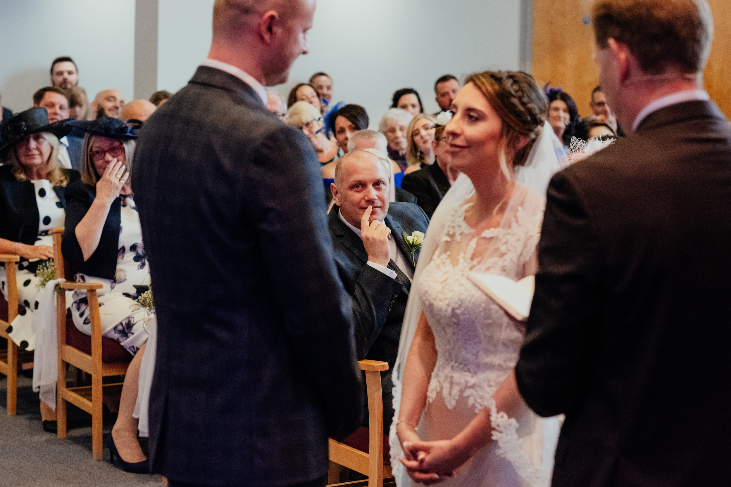 Bride and Groom exchange vows as Father of the Bride sheds a tear behind them