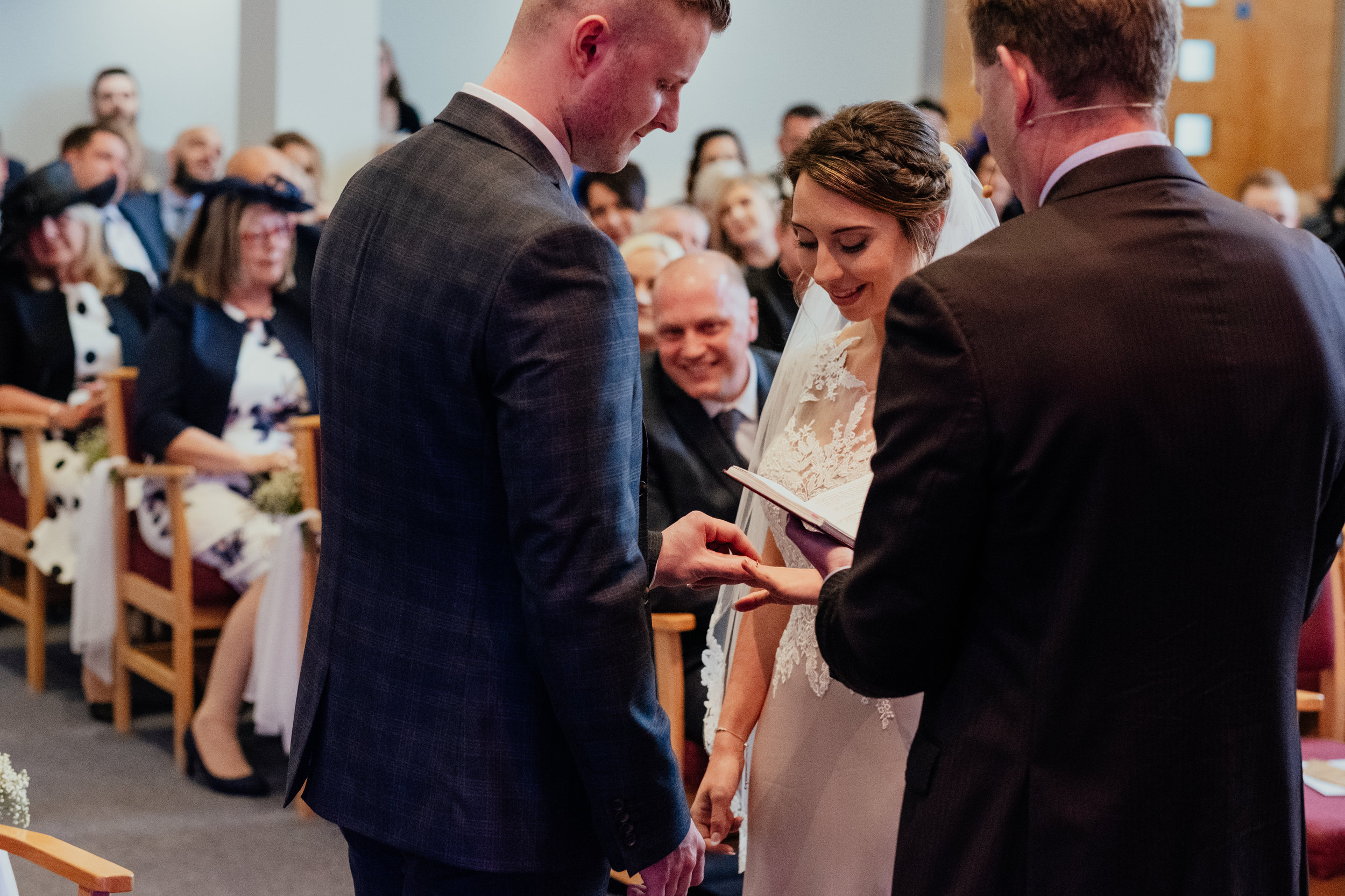 Groom puts rings on Bride's finger