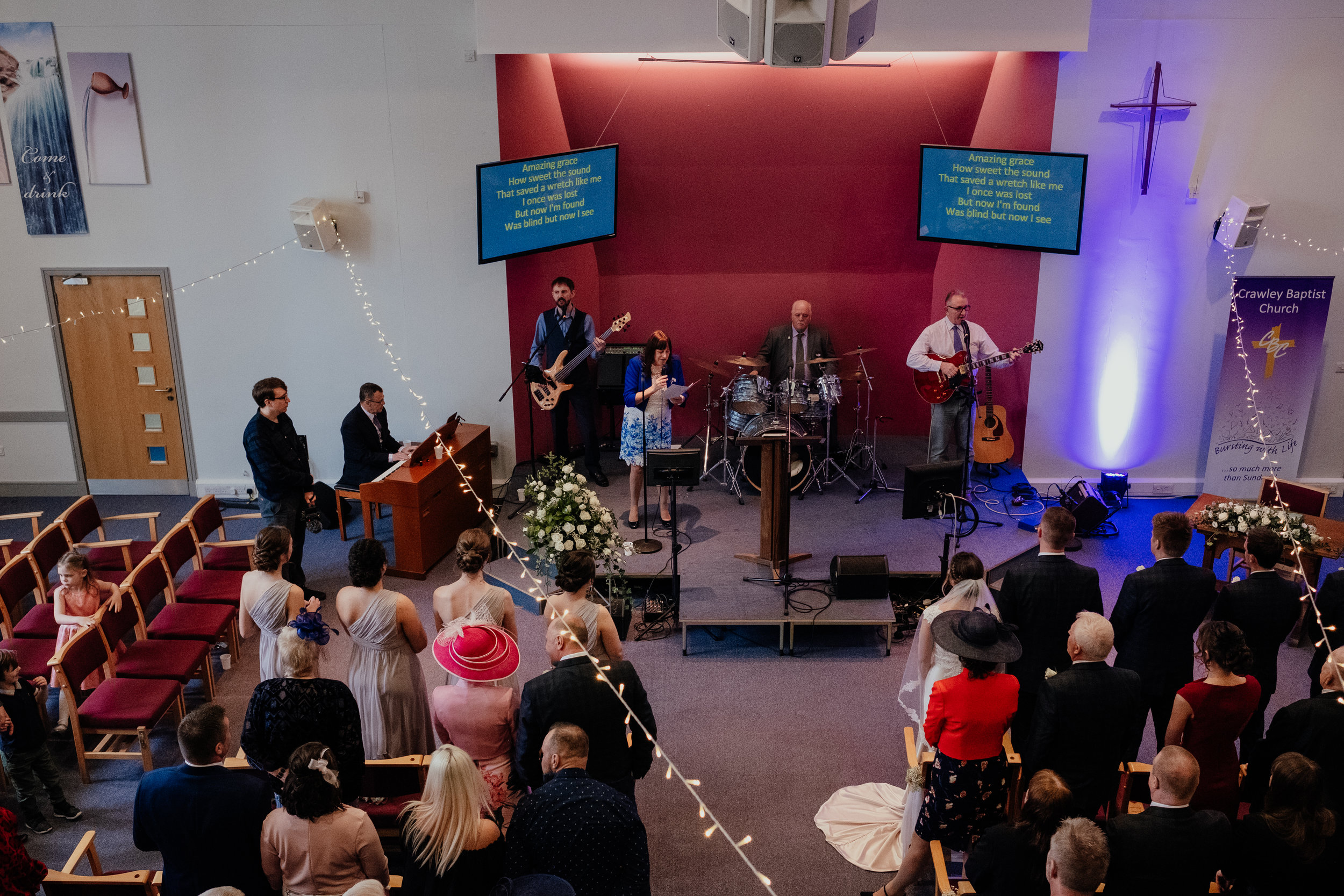 Bride and Groom and guests singing along to hymn performed by band in church
