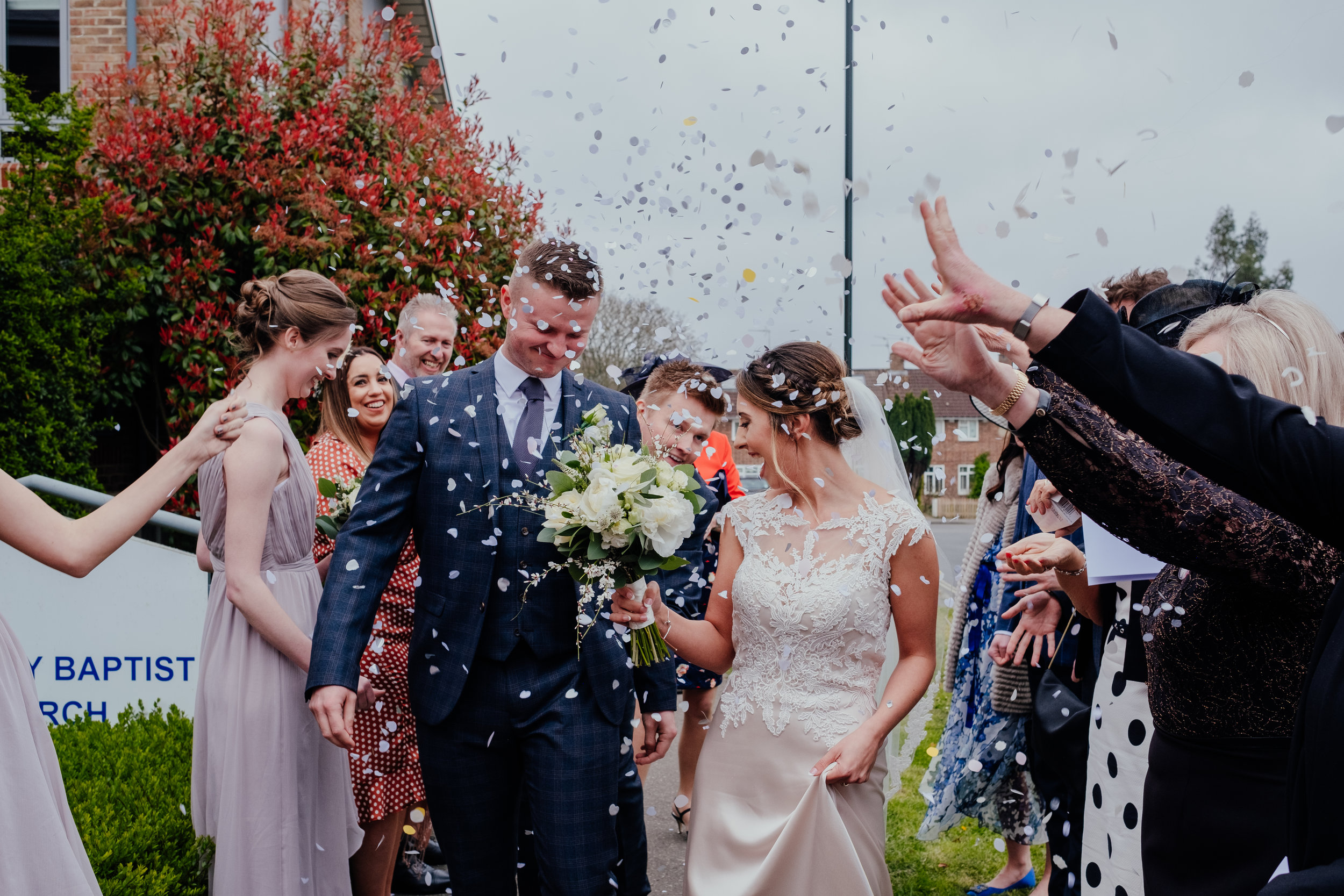 Guests throw confetti over newlyweds