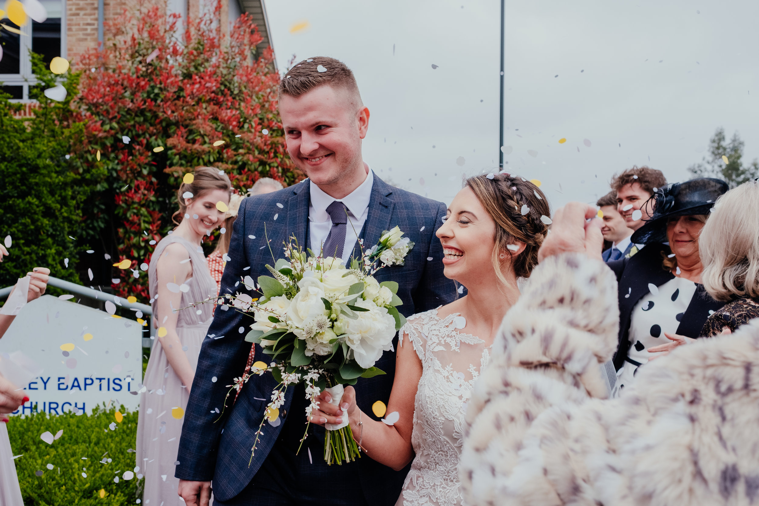 Bride and Groom smile as guests throw confetti