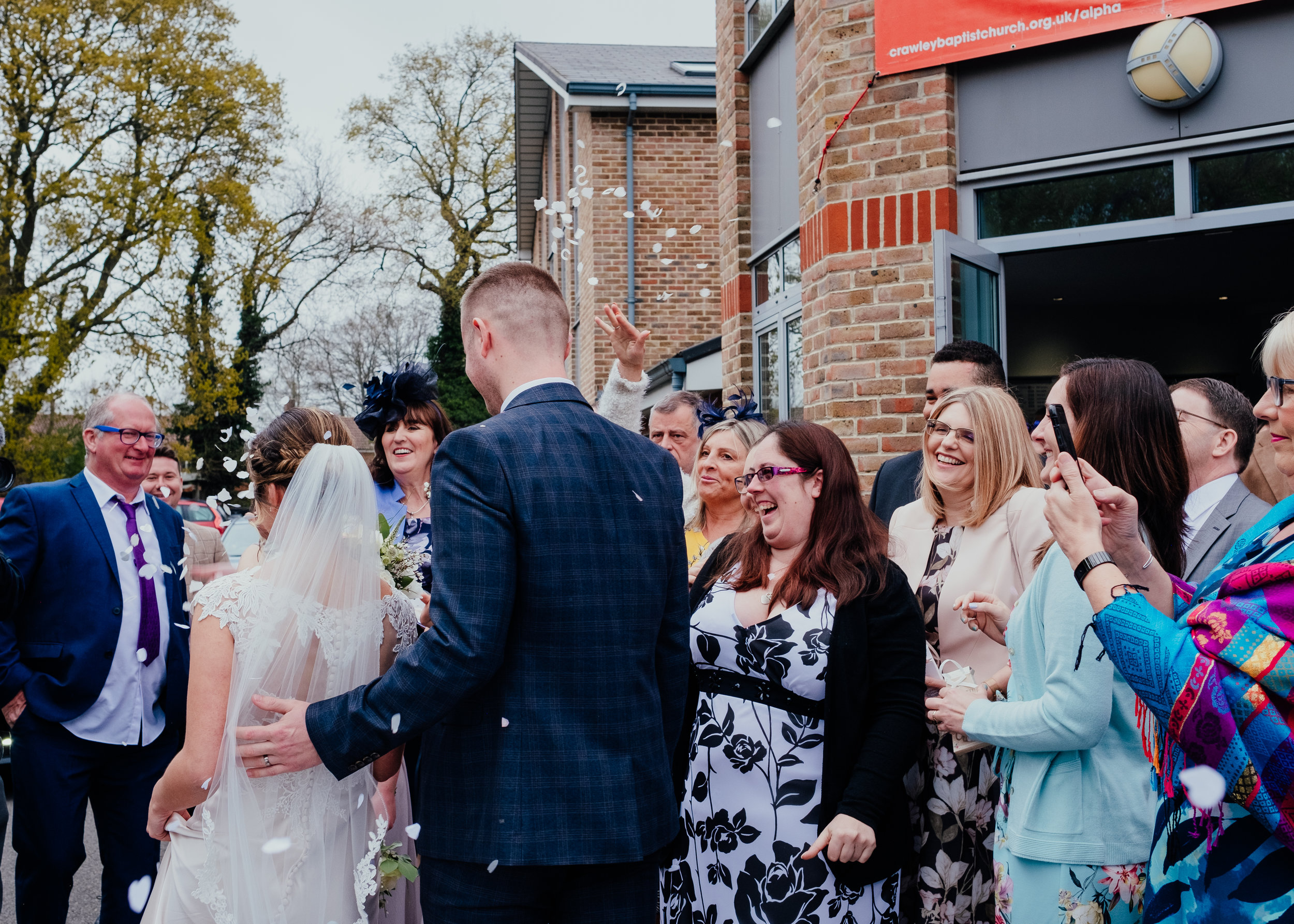 Family and friends throw confetti over Bride and Groom