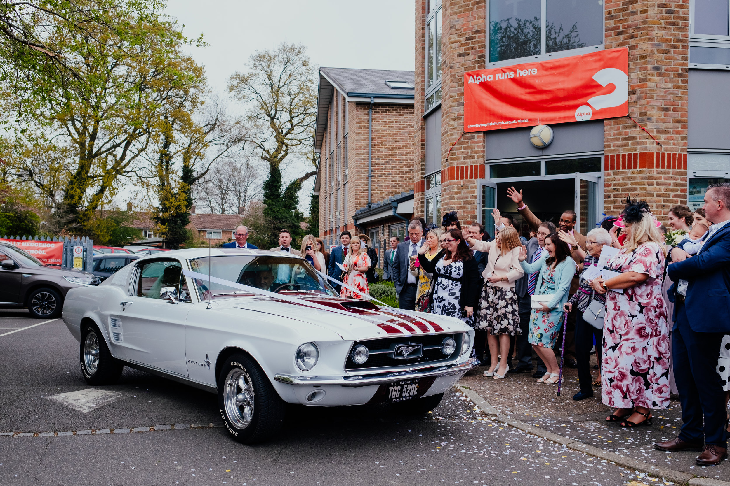 Guests wave as Bride and Groom drive away in a Mustang wedding car
