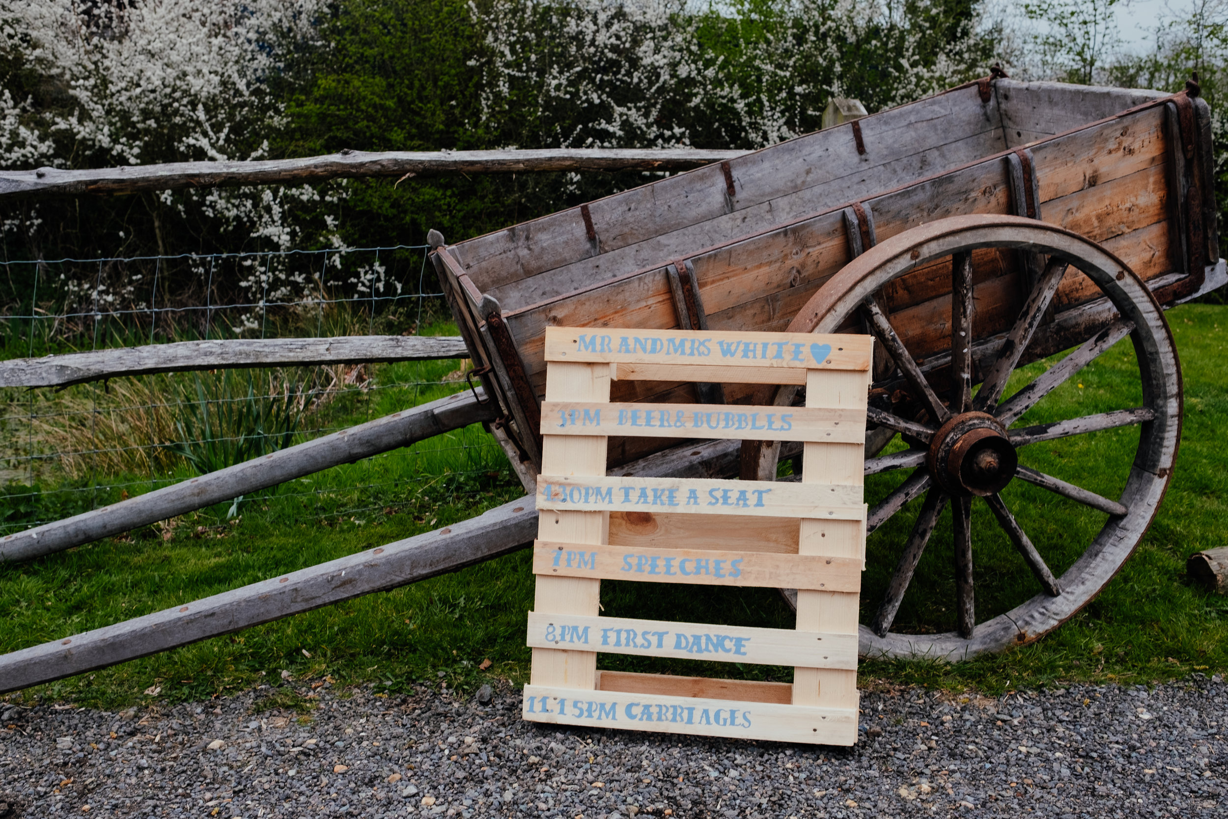 Rustic pallet order of the day sign at wedding leaning against wooden cart