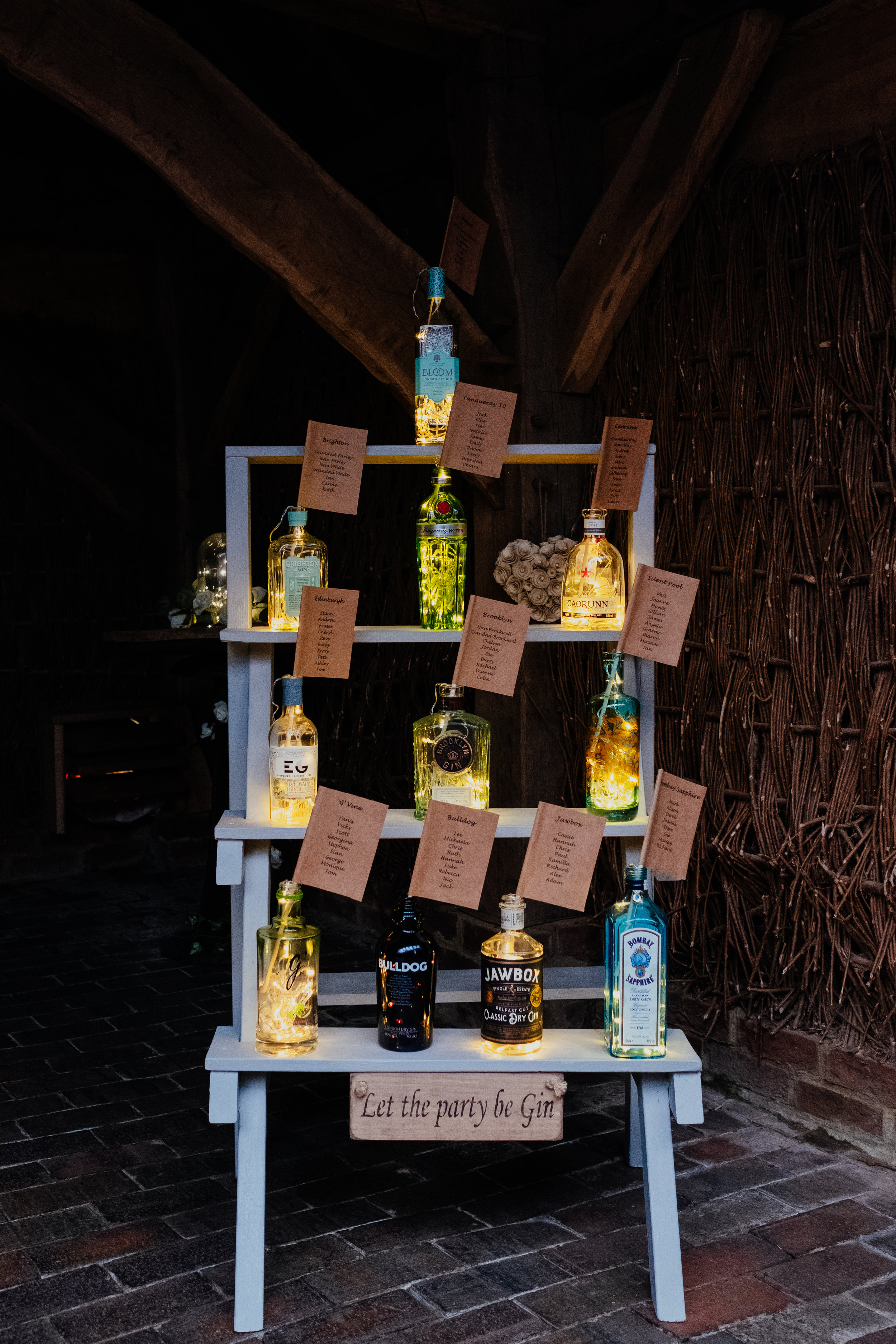Rustic wedding table plan with gin bottles and fairy lights