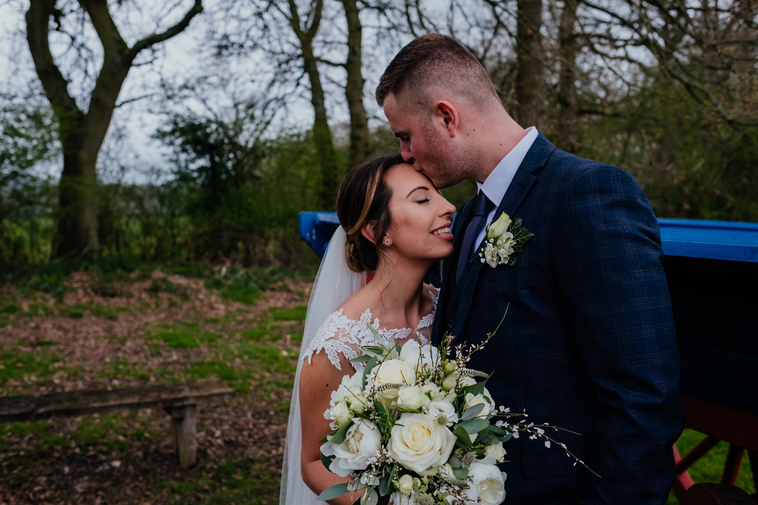 Groom kissing bride on forehead   Gildings Barn wedding photography