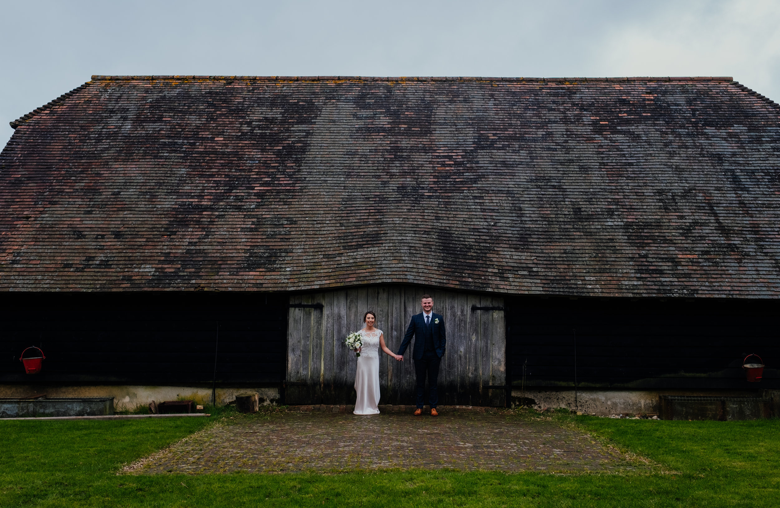 Bride and Groom stood outside barn | Gildings Barn Wedding Photography