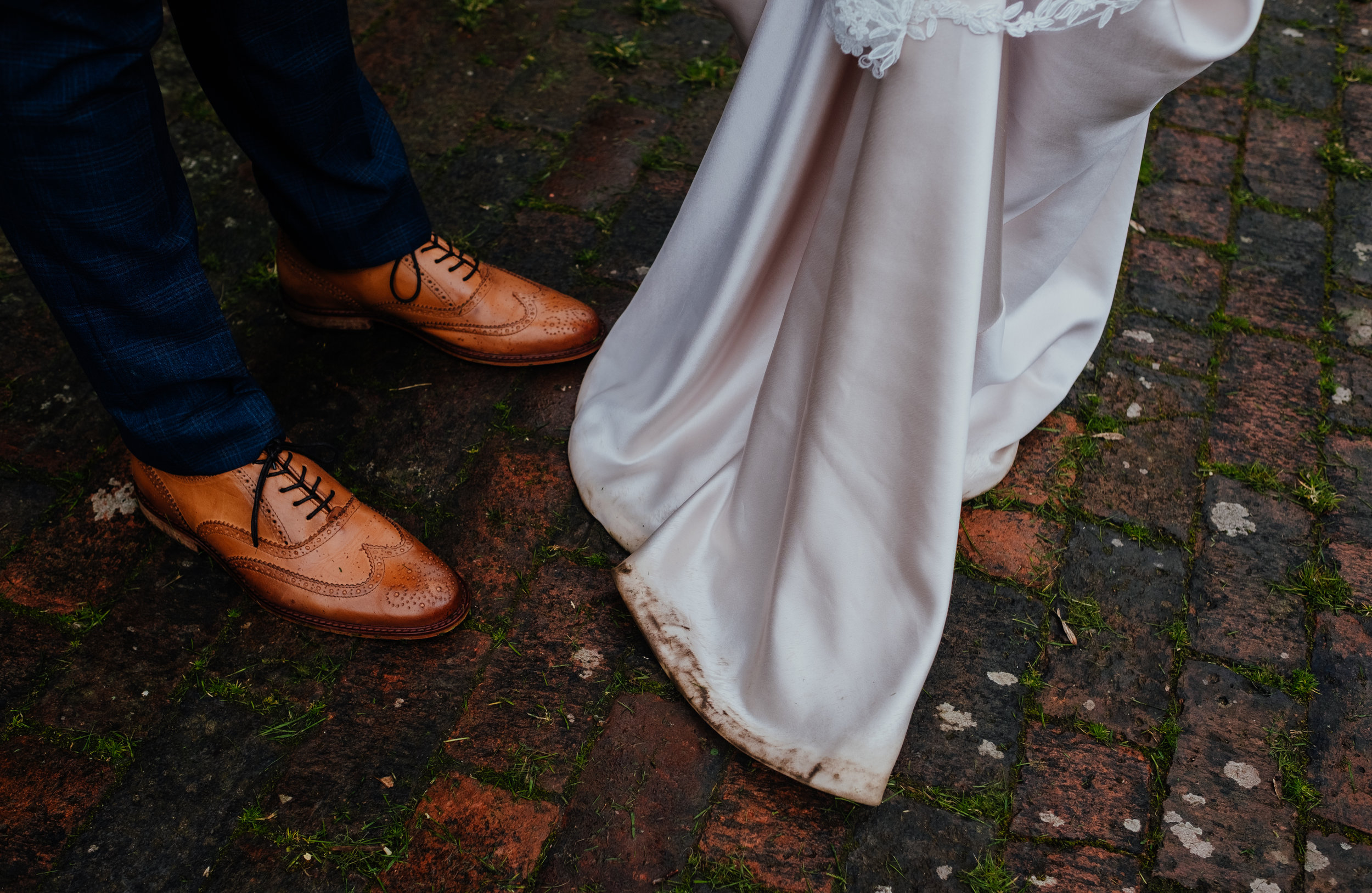 Groom's shoes and the dirty bottom of bride's wedding dress