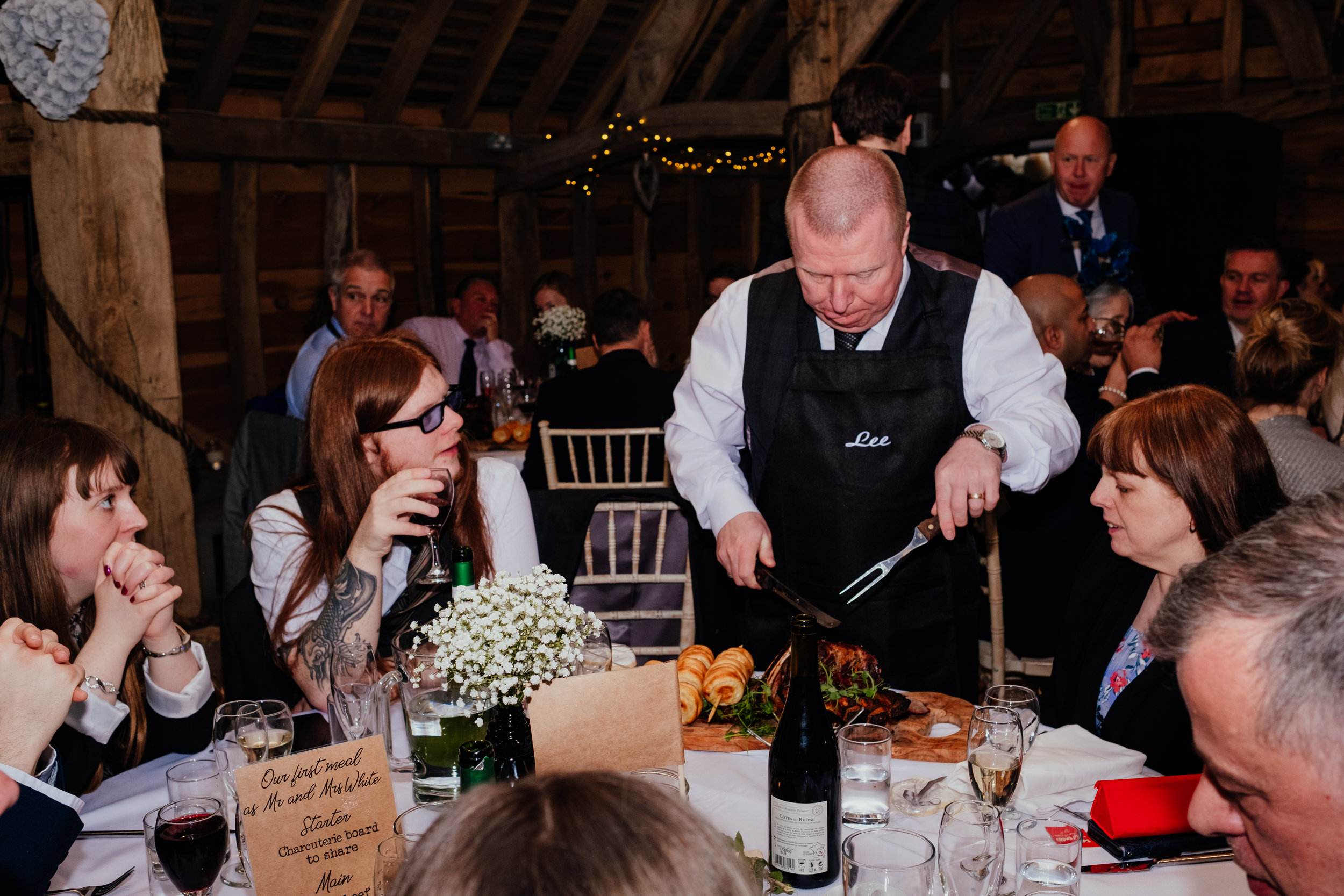 Wedding guests carve meat at their table