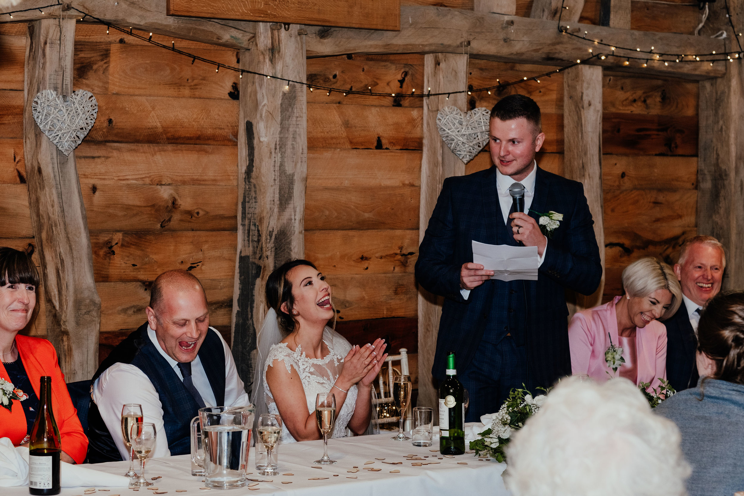 Groom speech at Gildings Barn while guests laugh