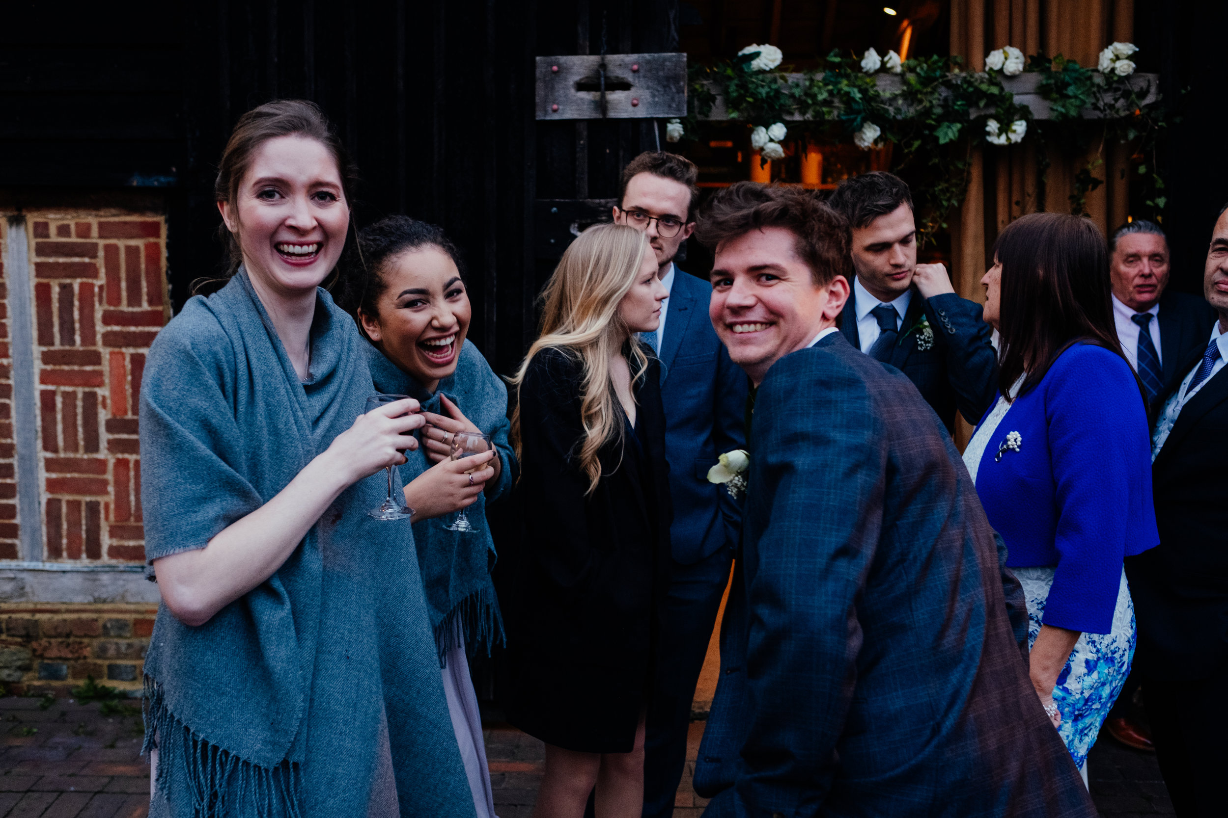 Wedding guests and bridesmaids laughing during wedding reception at Gildings Barn