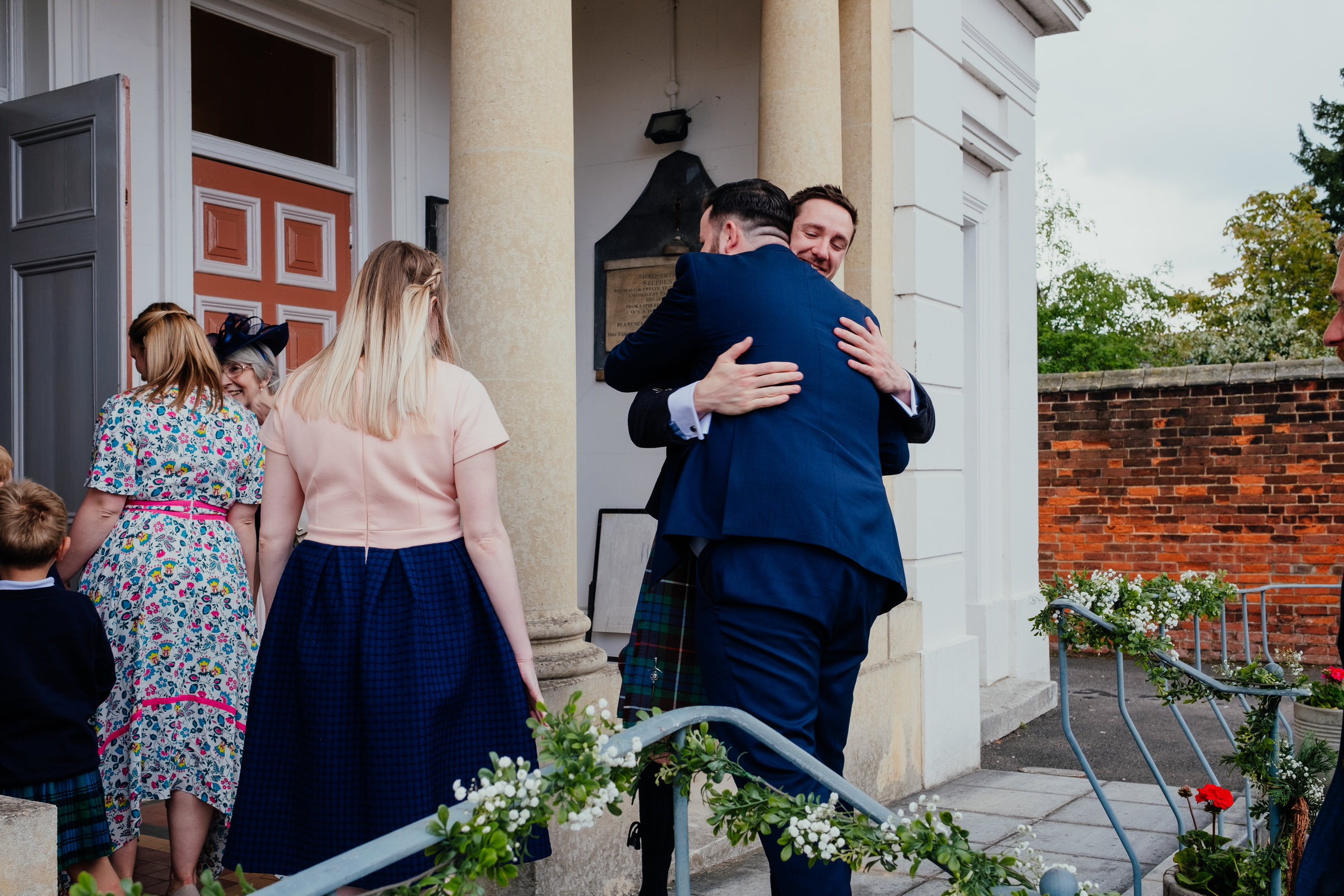 Groom hugs guests as they arrive for the wedding