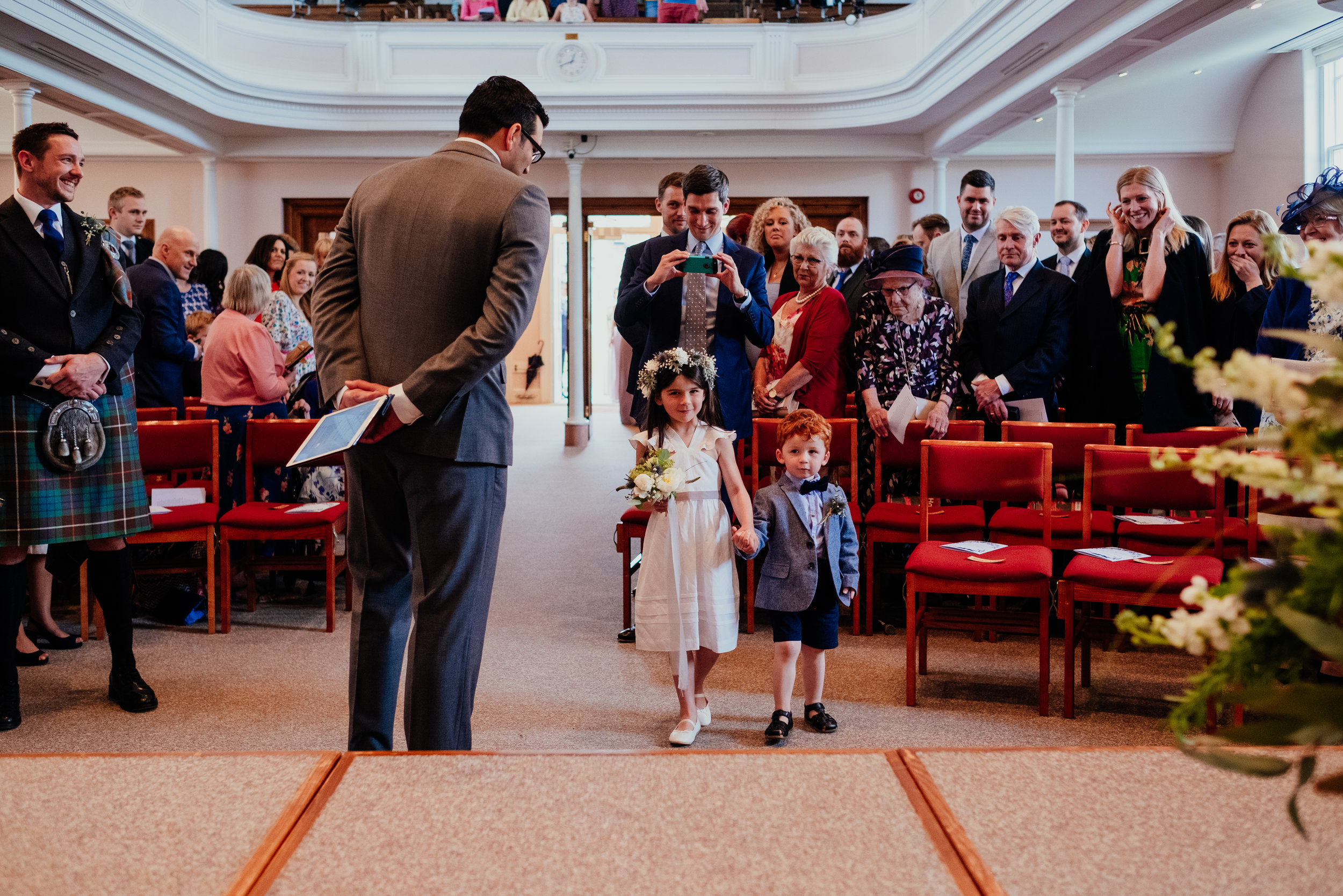 Groom and wedding guests smile at flower girl and page boy as they walk down the aisle