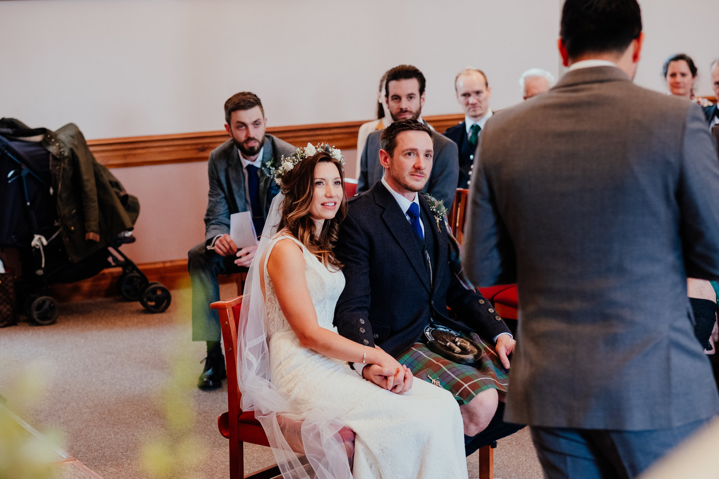 Bride and Groom sat down holding hands