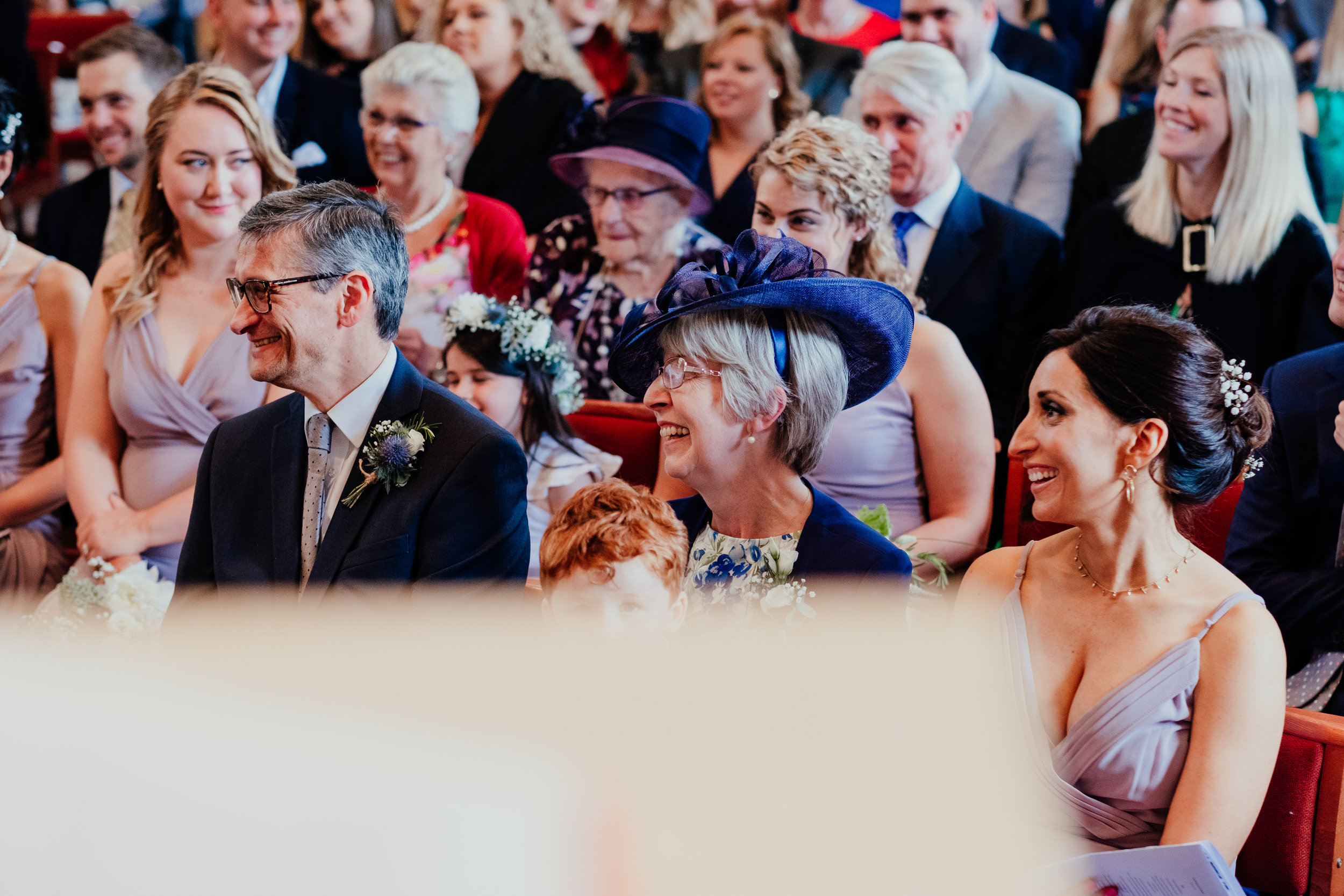 Wedding guests laughing during wedding ceremony
