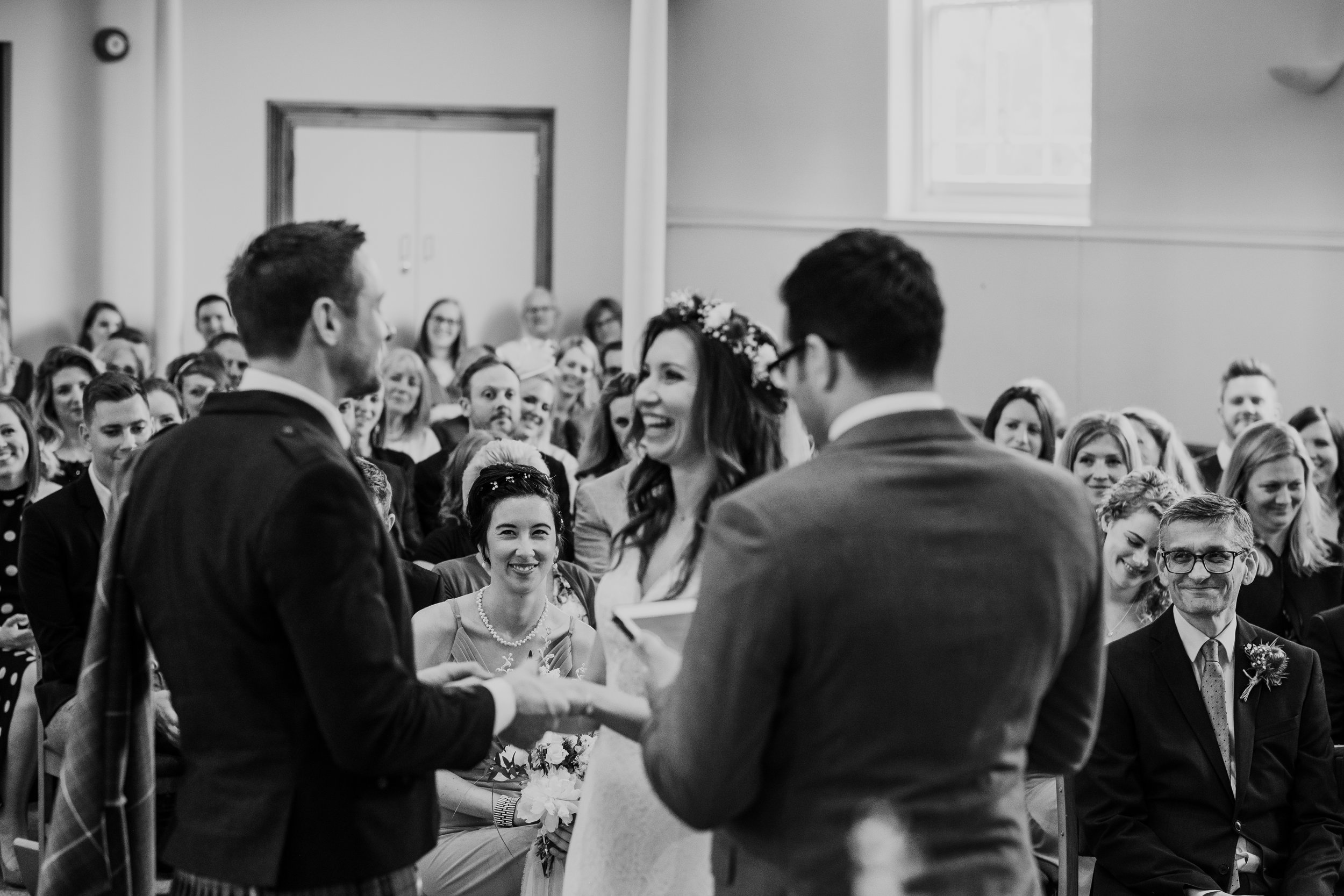 Bridesmaid and Father of Bride smile as Bride and Groom exchange vows