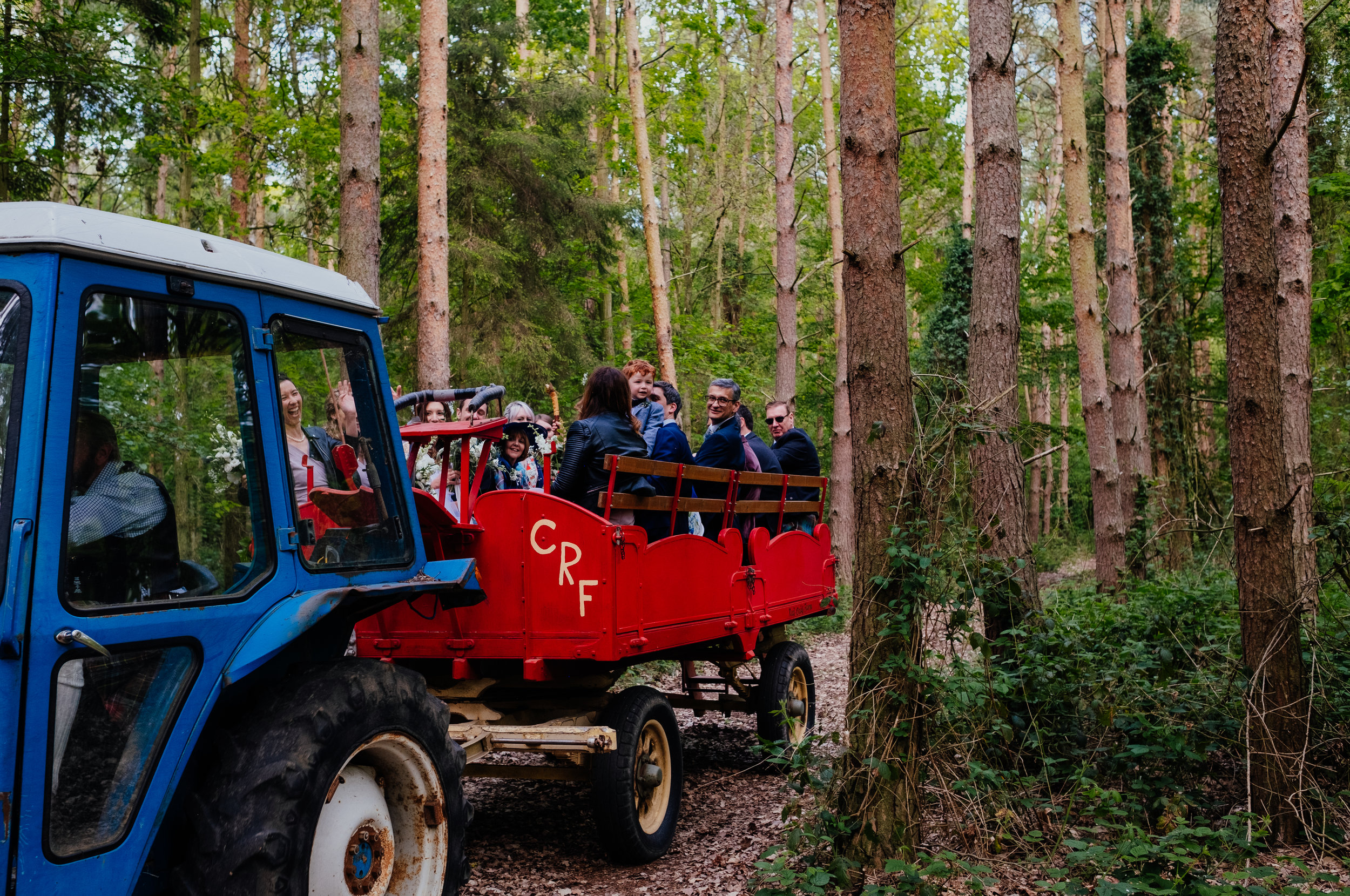 Captains Wood Barn wedding tractor and cart carrying wedding party