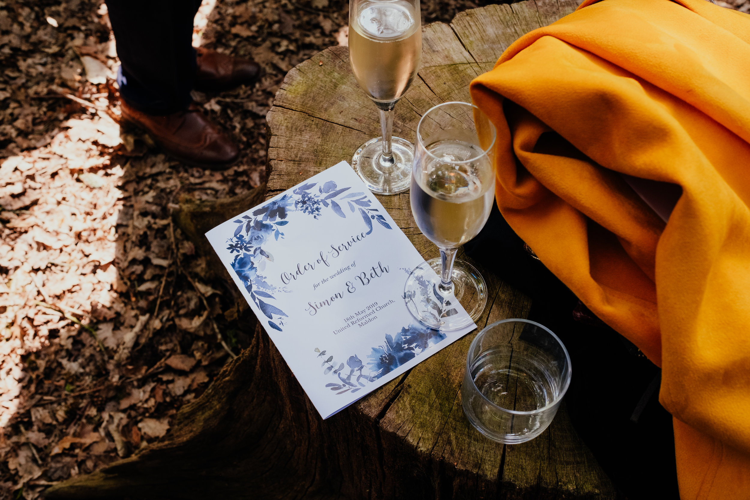 Floral Wedding Order of Service resting on tree trunk next to yellow coat and glasses of champagne
