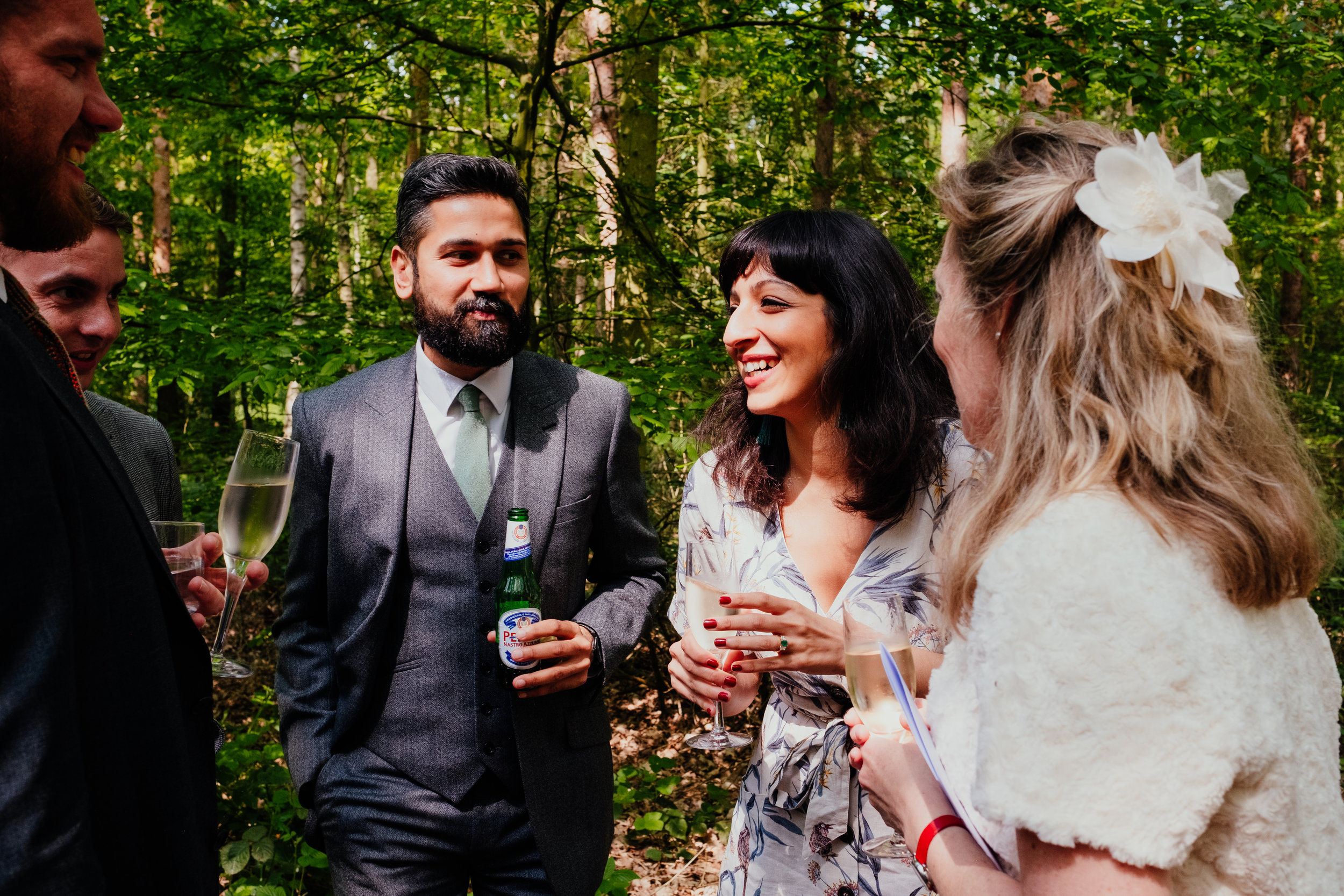 Wedding guests drinking champagne during drinks reception at Captains Wood Barn