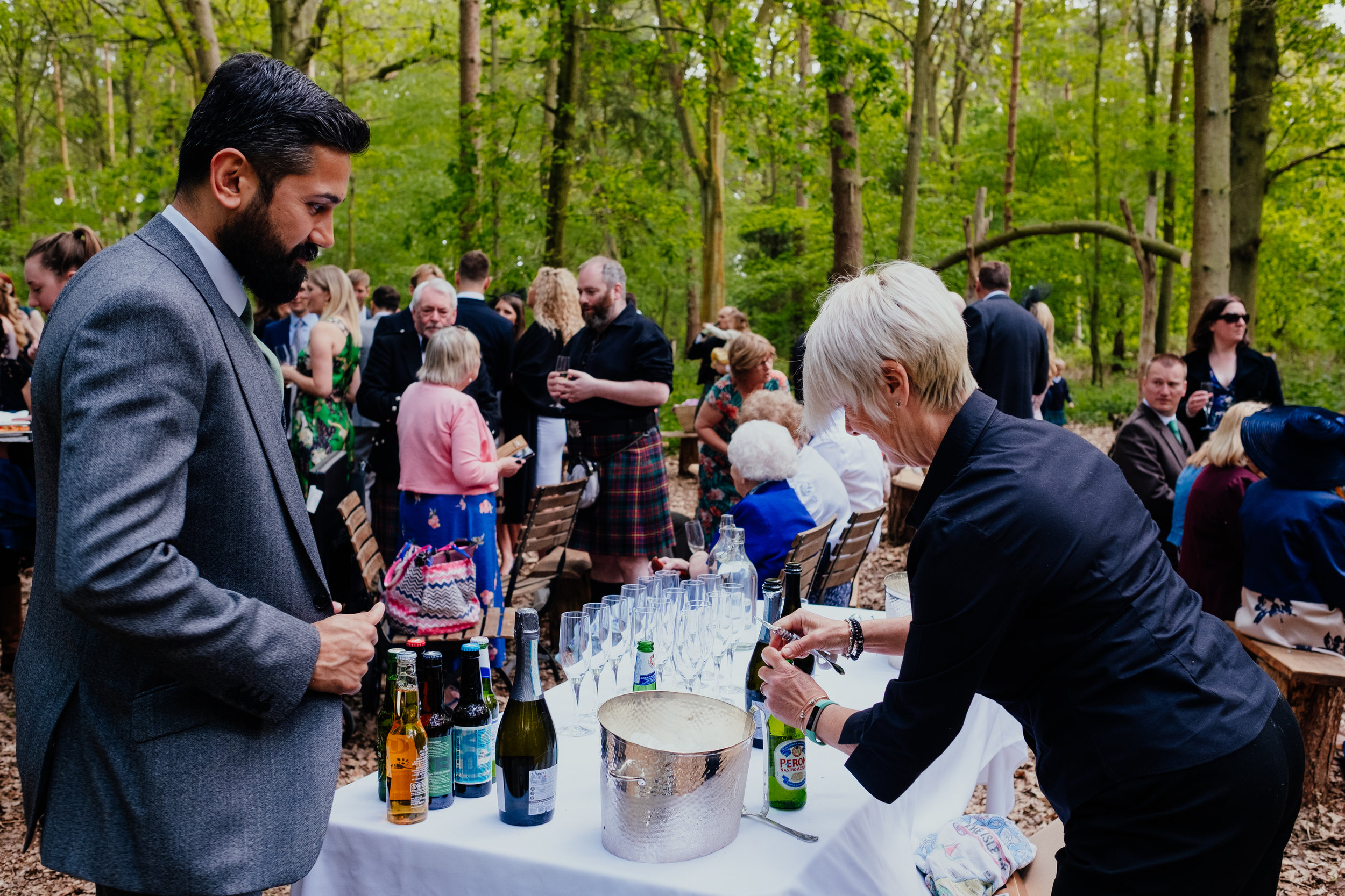 Wedding guest asks for beer by bar staff during outdoor drinks reception at Captains Wood Barn
