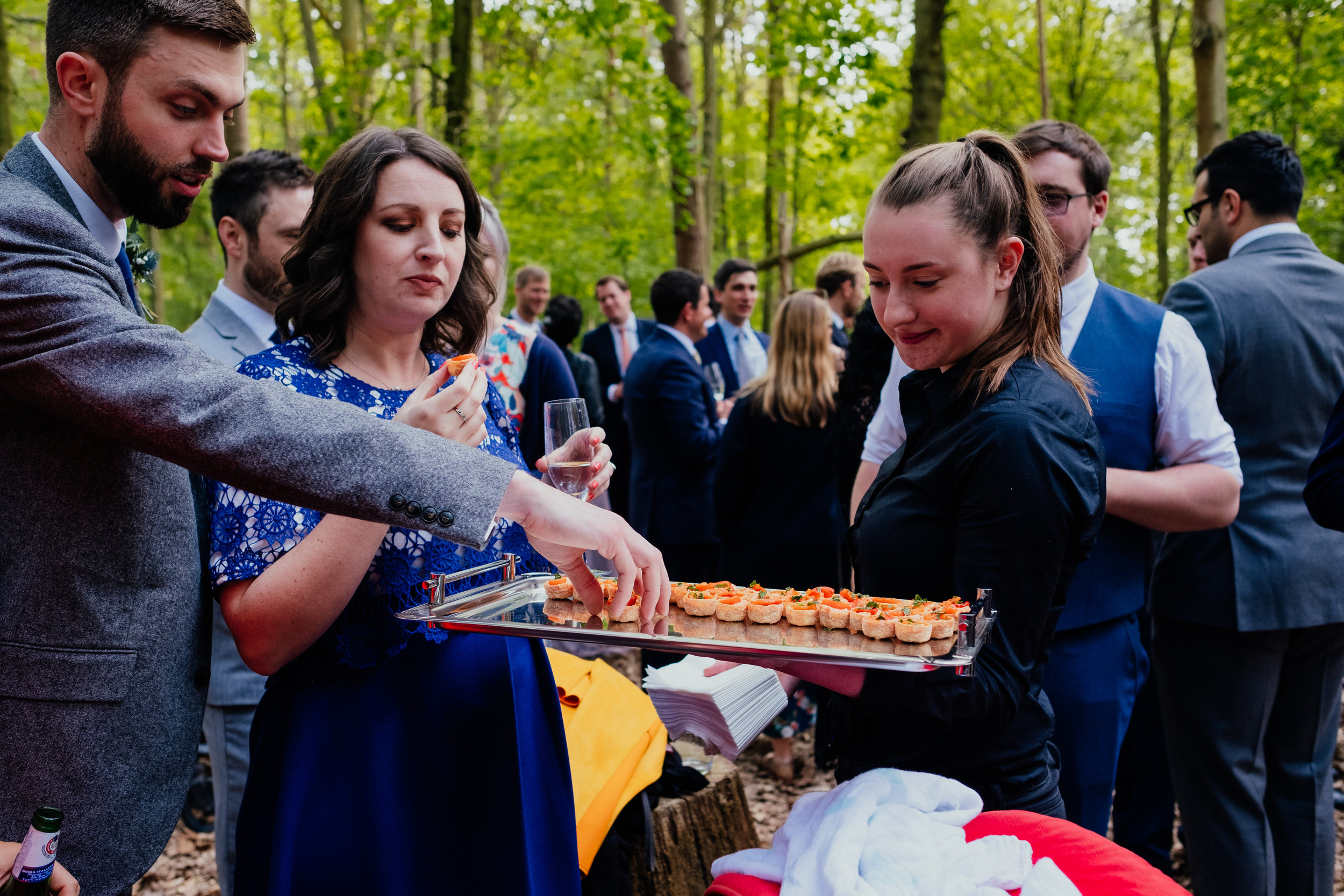 Wedding guests eat canapés during outdoor drinks reception at Captains Wood Barn wedding