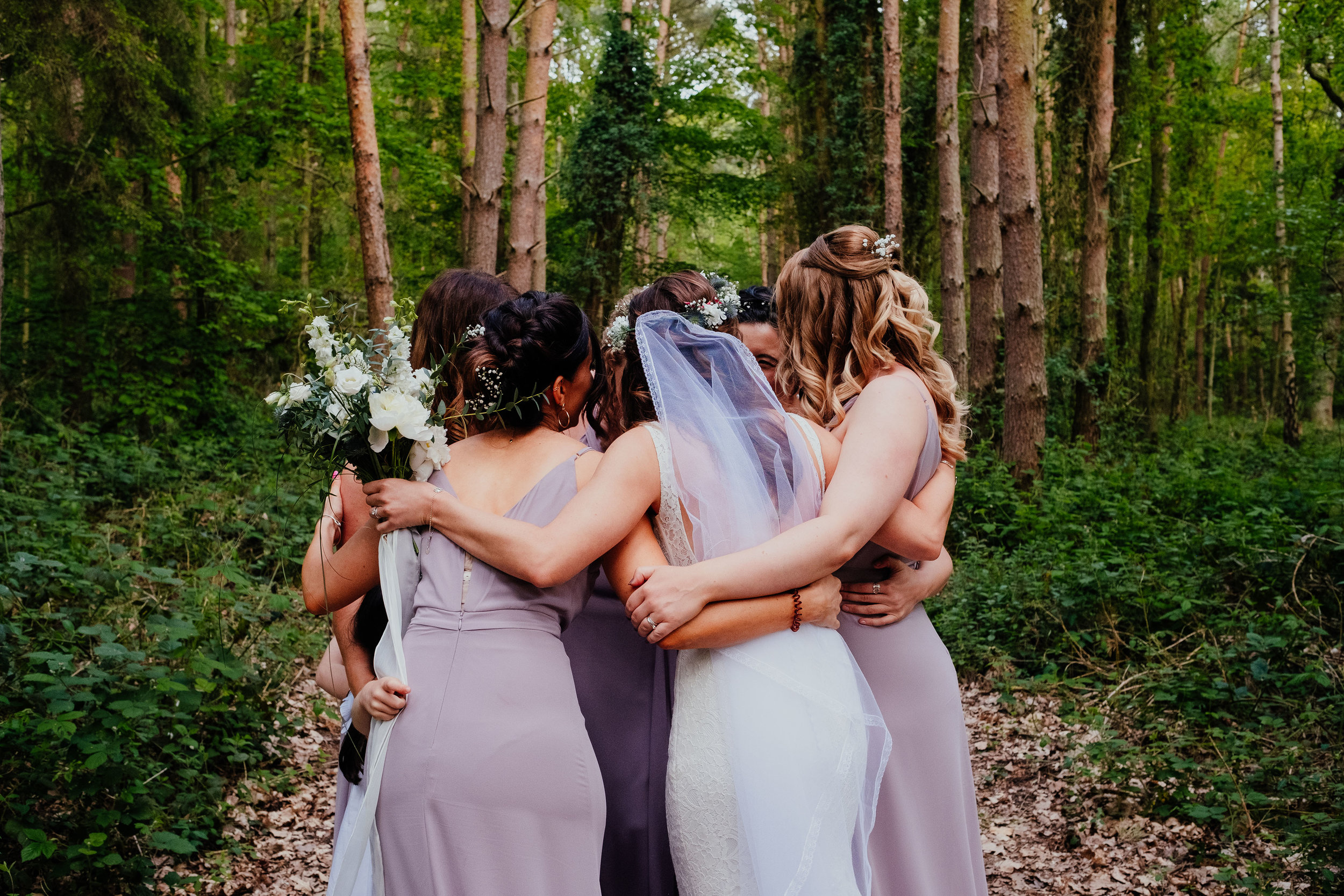 Bride hugging bridesmaids at Captains Wood Barn wedding