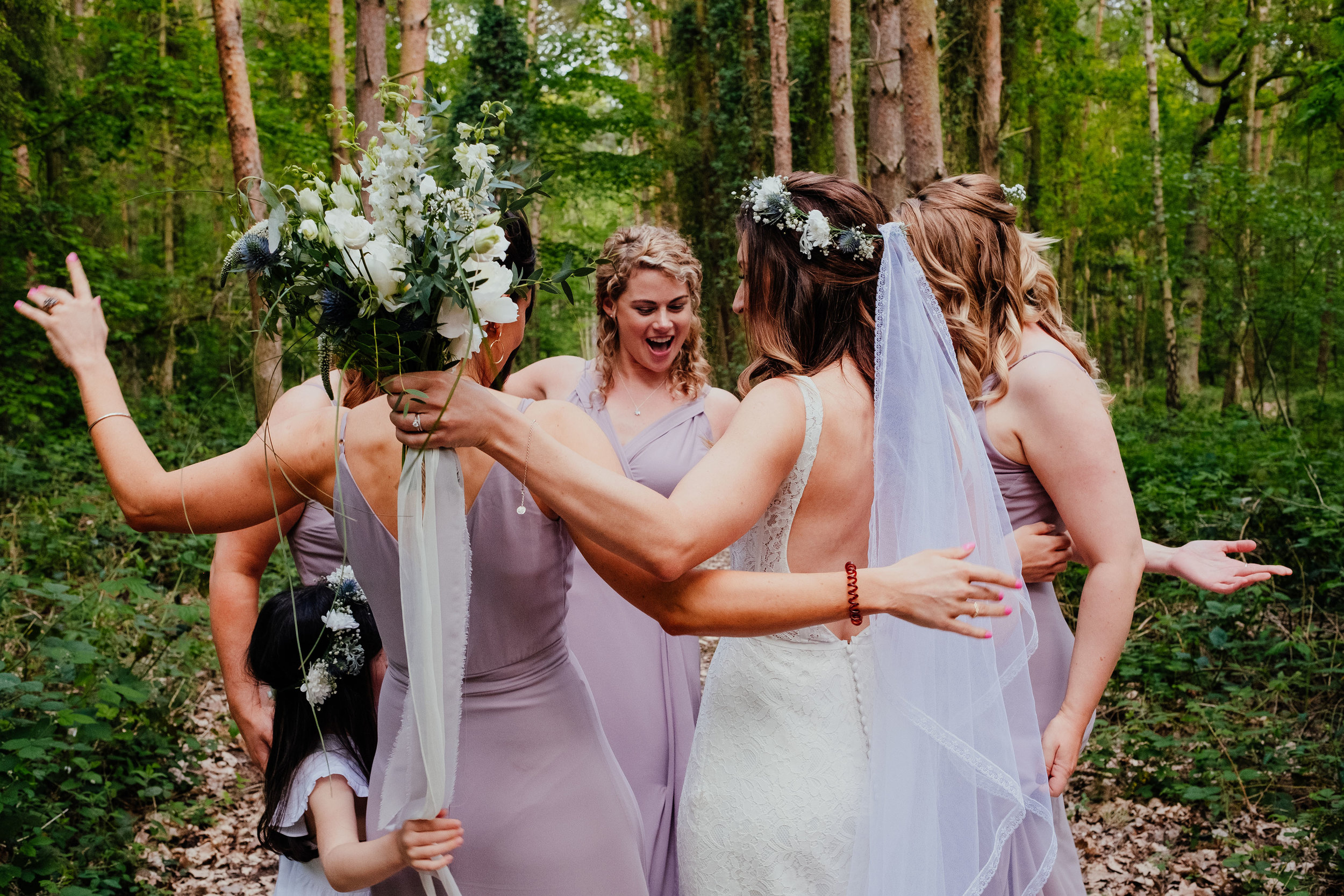 Bride dancing with bridesmaids in the woods at Captains Wood Barn wedding