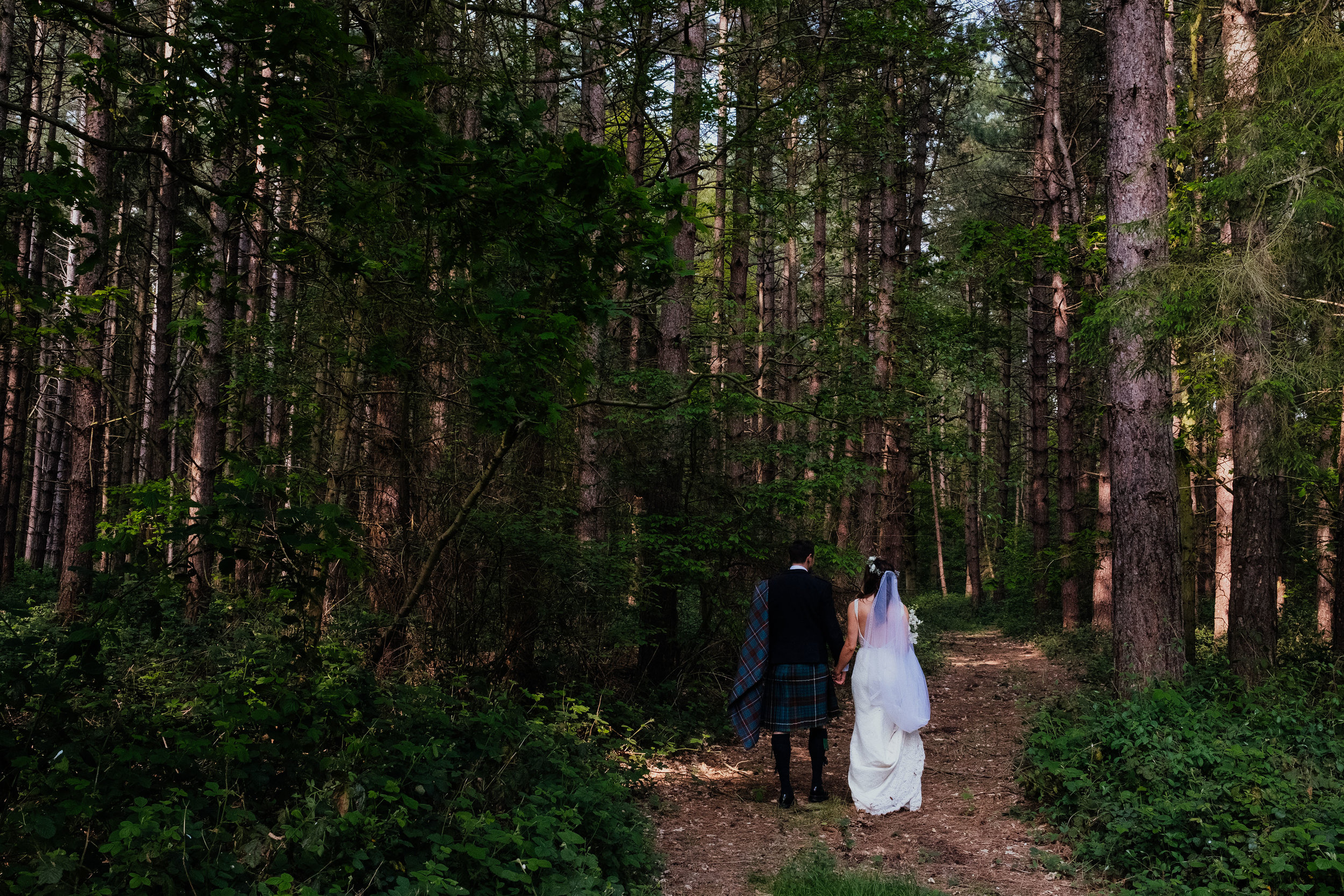 Bride and groom walk through pine forest at Captains Wood Barn wedding