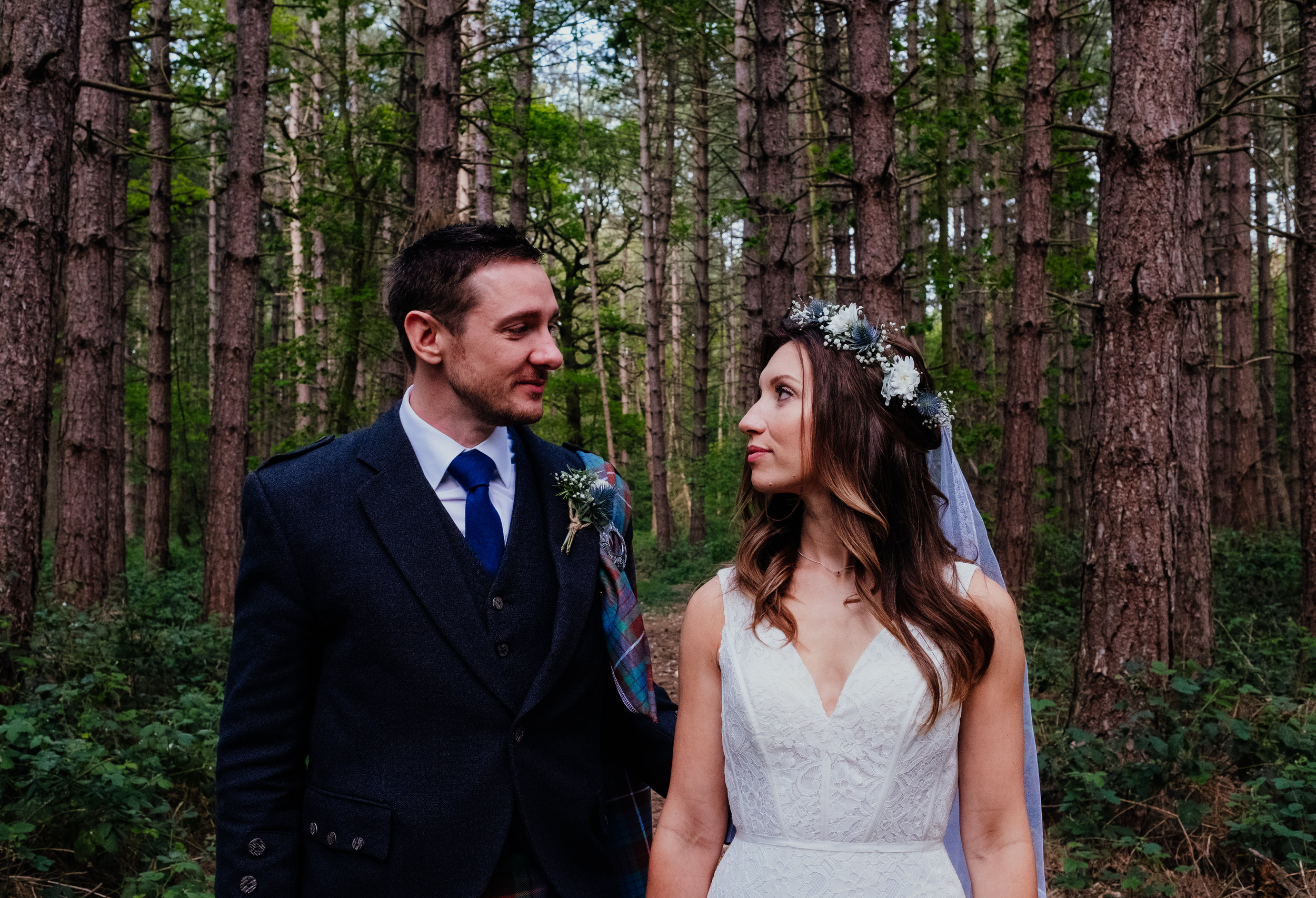 Bride and Groom look at each other stood in the woodland at Captains Wood Barn wedding